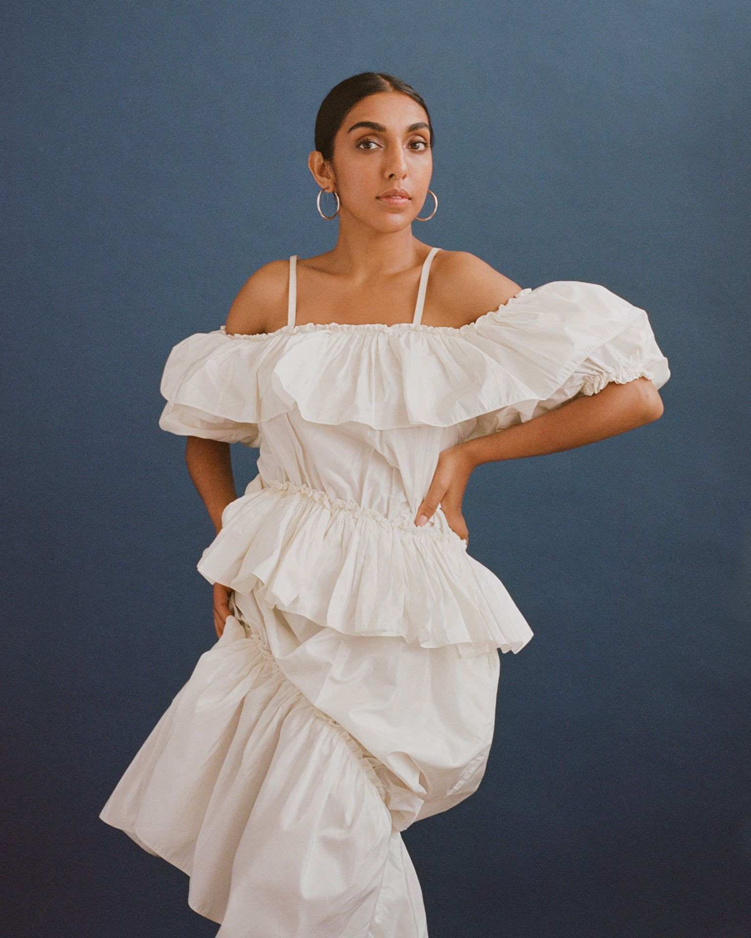 writer Rupi Kaur on blue background looking at camera wearing white dress by Oumayma B Tanfous for Vogue Espana