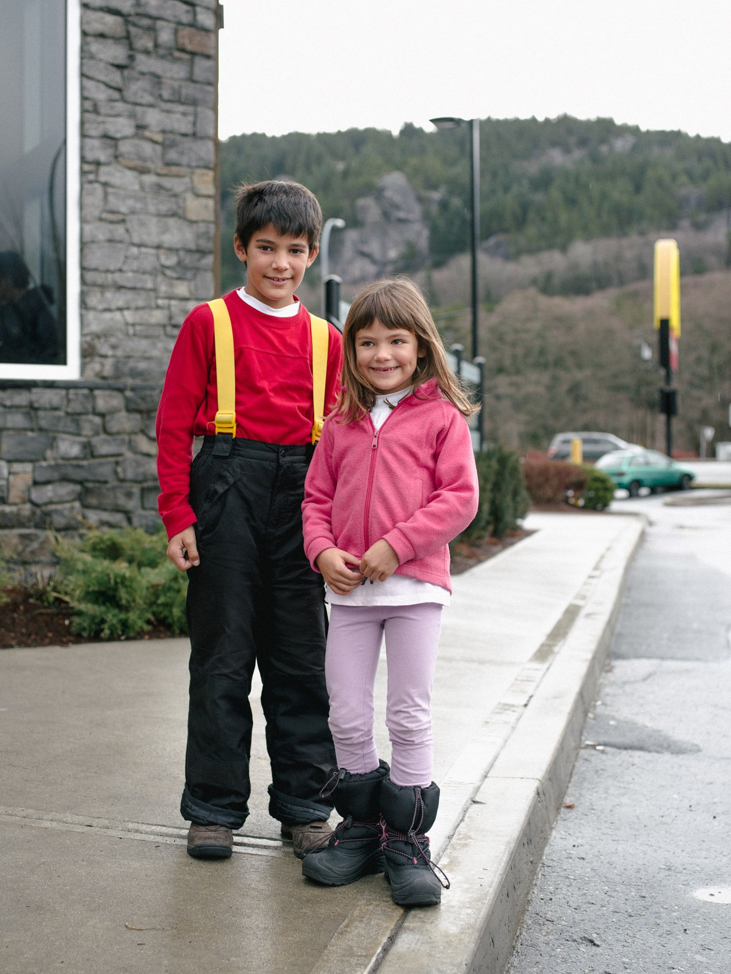 two kids outside smiling wearing snow pants by Alexi Hobbs for McDonald's