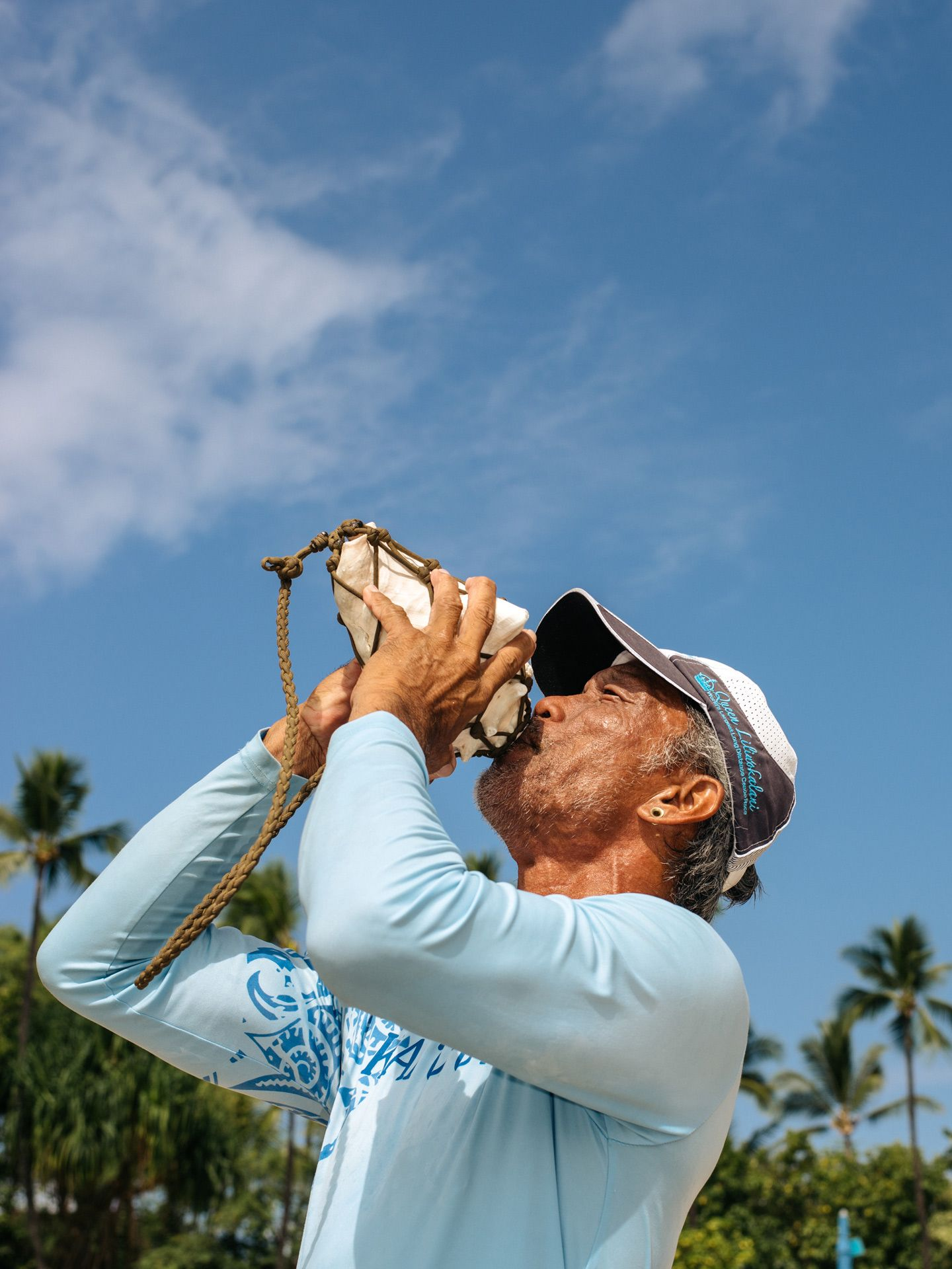 hawaiian male native blowing into big seashell conch by Alexi Hobbs in Hawaii for enRoute