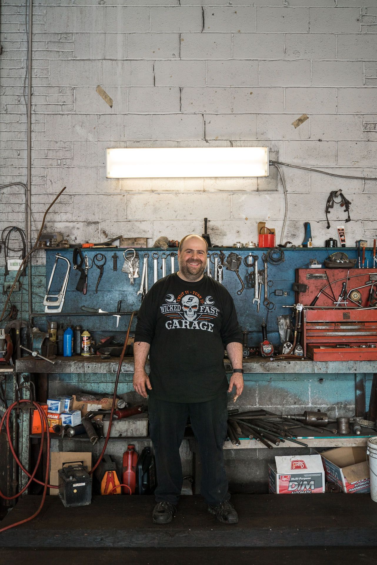 bald garage owner smiling posing in front of his work table with tools by Bruno Florin for Mile-Ex Milles vie