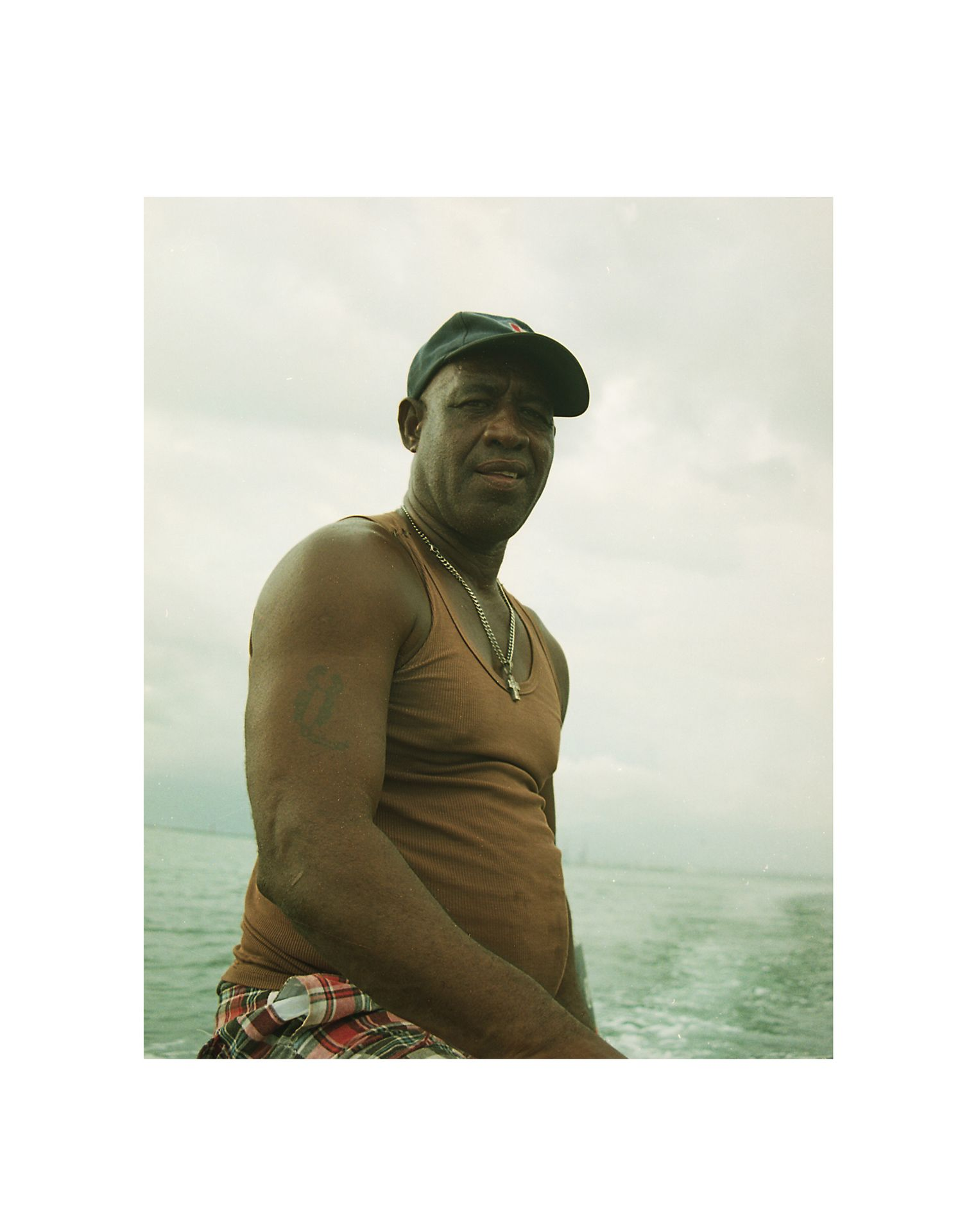 jamaican man boat driver looking at camera by Oumayma B Tanfous in Jamaica