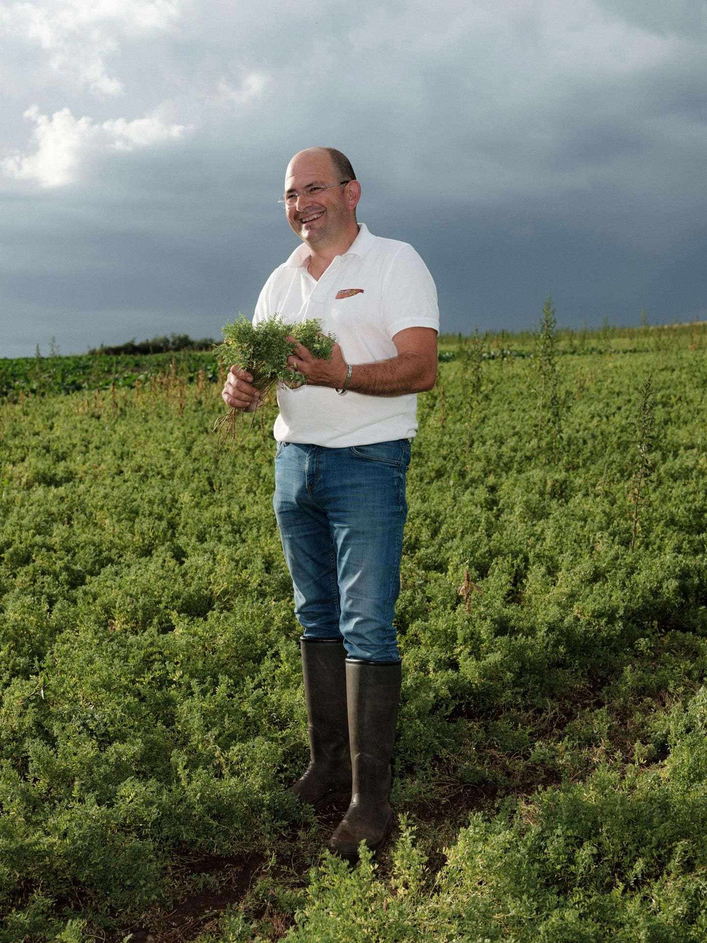 farmer man in his field laughing showing off his crop by Alexi Hobbs in Auvergne for Reflets de France
