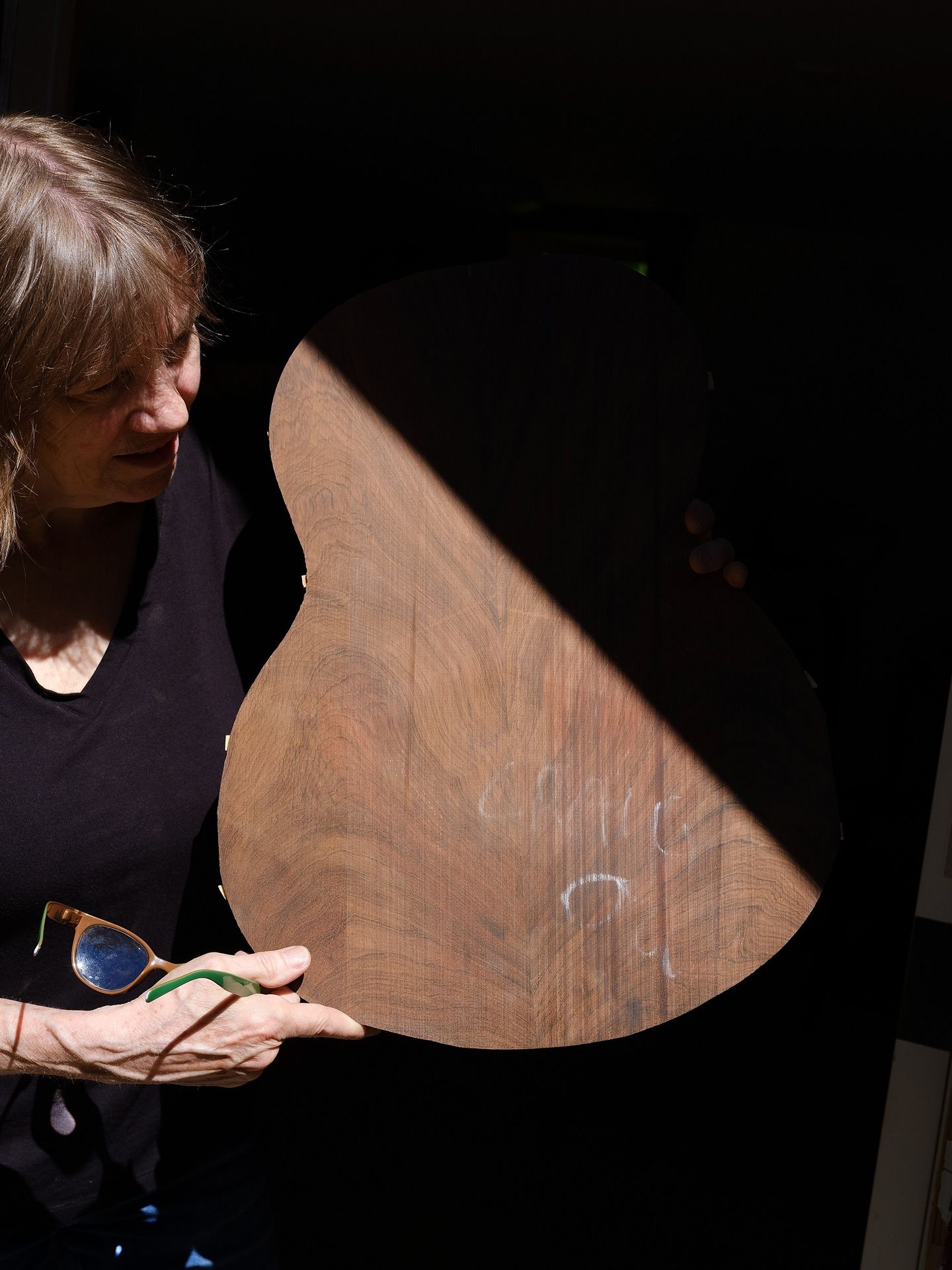 woman holding unvarnished guitar inspecting the back by Guillaume Simoneau for Mercedes Benz Magazine