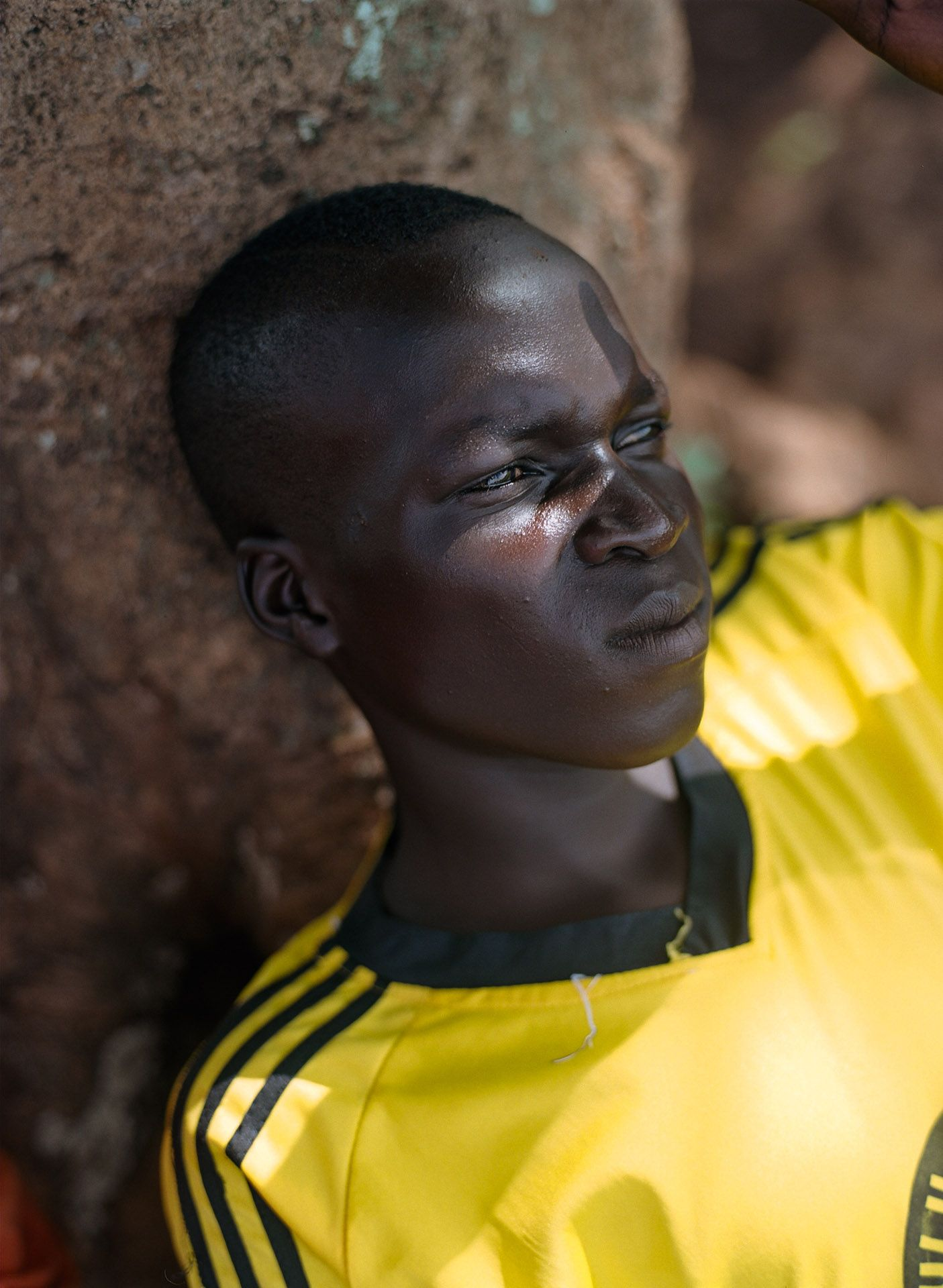 young black boy resting in the shade against a tree by Alexi Hobbs in Uganda for Football for good with Sportsnet