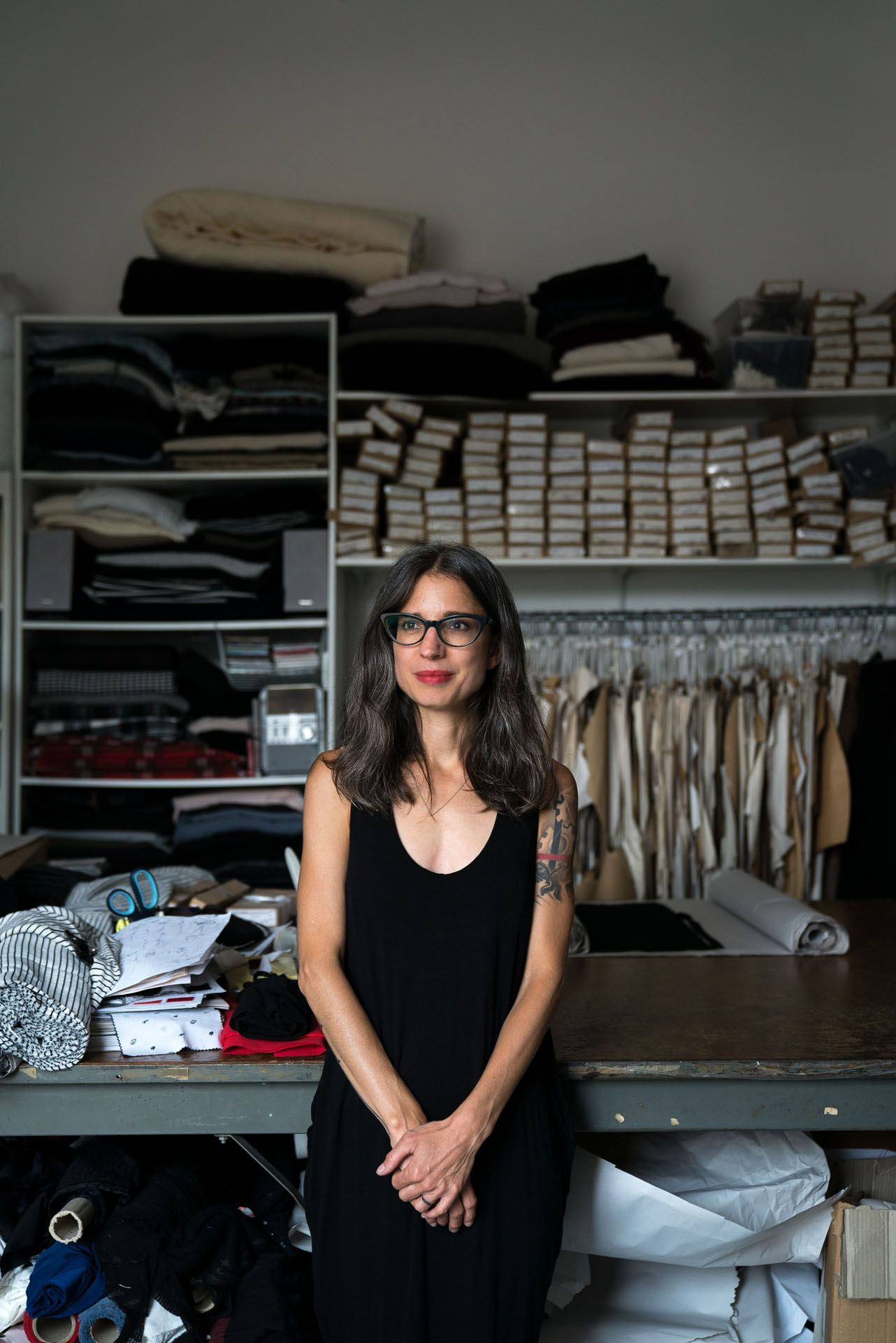 brown haired woman seamstress looking away posing in front of worktable with scissors and piles of fabric by Bruno Florin for mile-ex mille vie