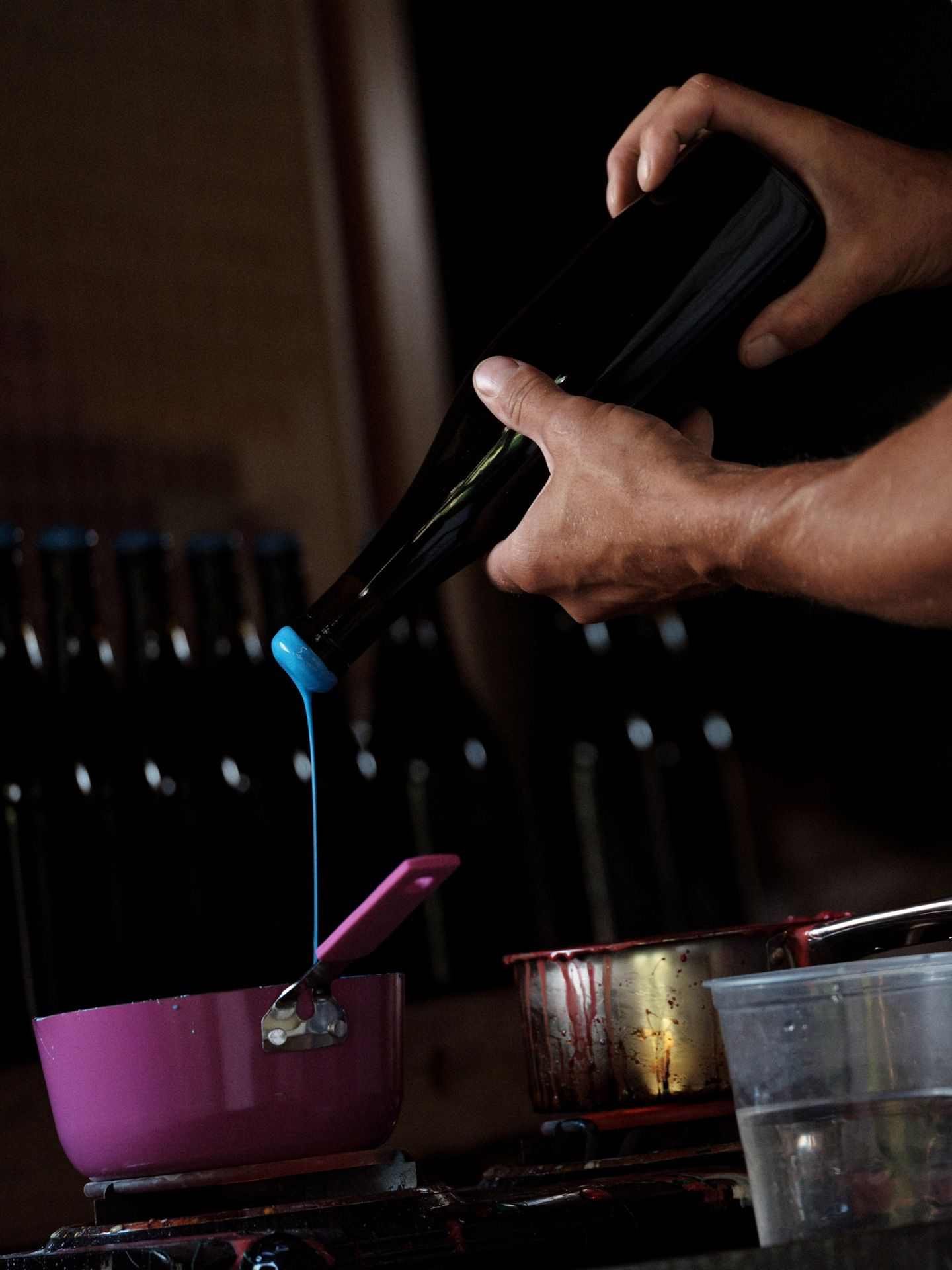 close up of winemaker from Pinard & Filles sealing wine bottles with light blue wax by Alexi Hobbs for Larose Paris