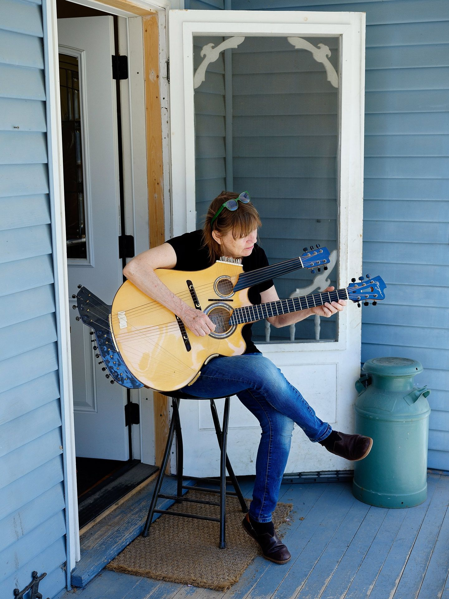 woman sitting on front porch playing large double head guitar by Guillaume Simoneau for Mercedes Benz Magazine