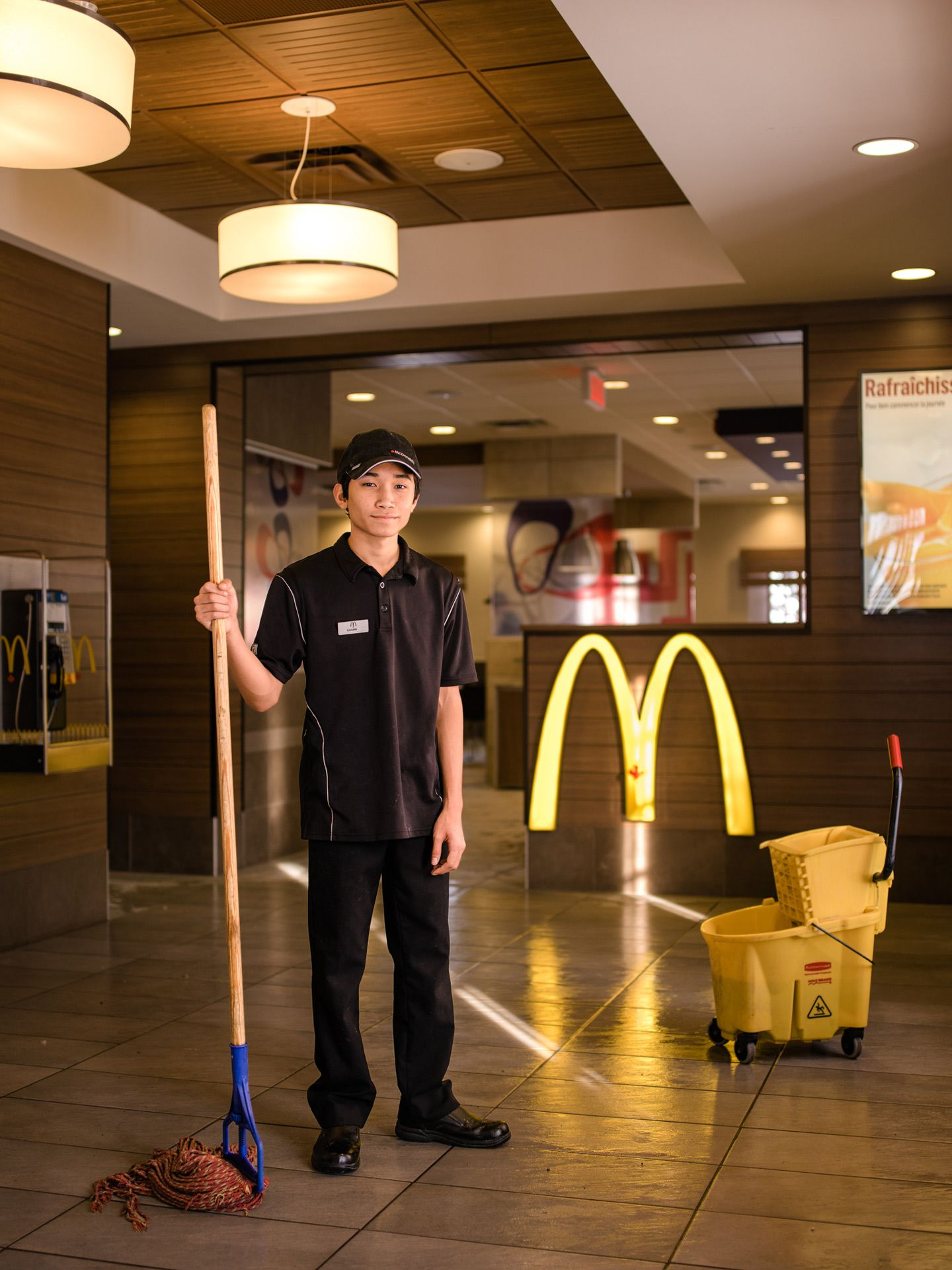 young male asian employee smiling at camera holding mop by Alexi Hobbs for McDonald's