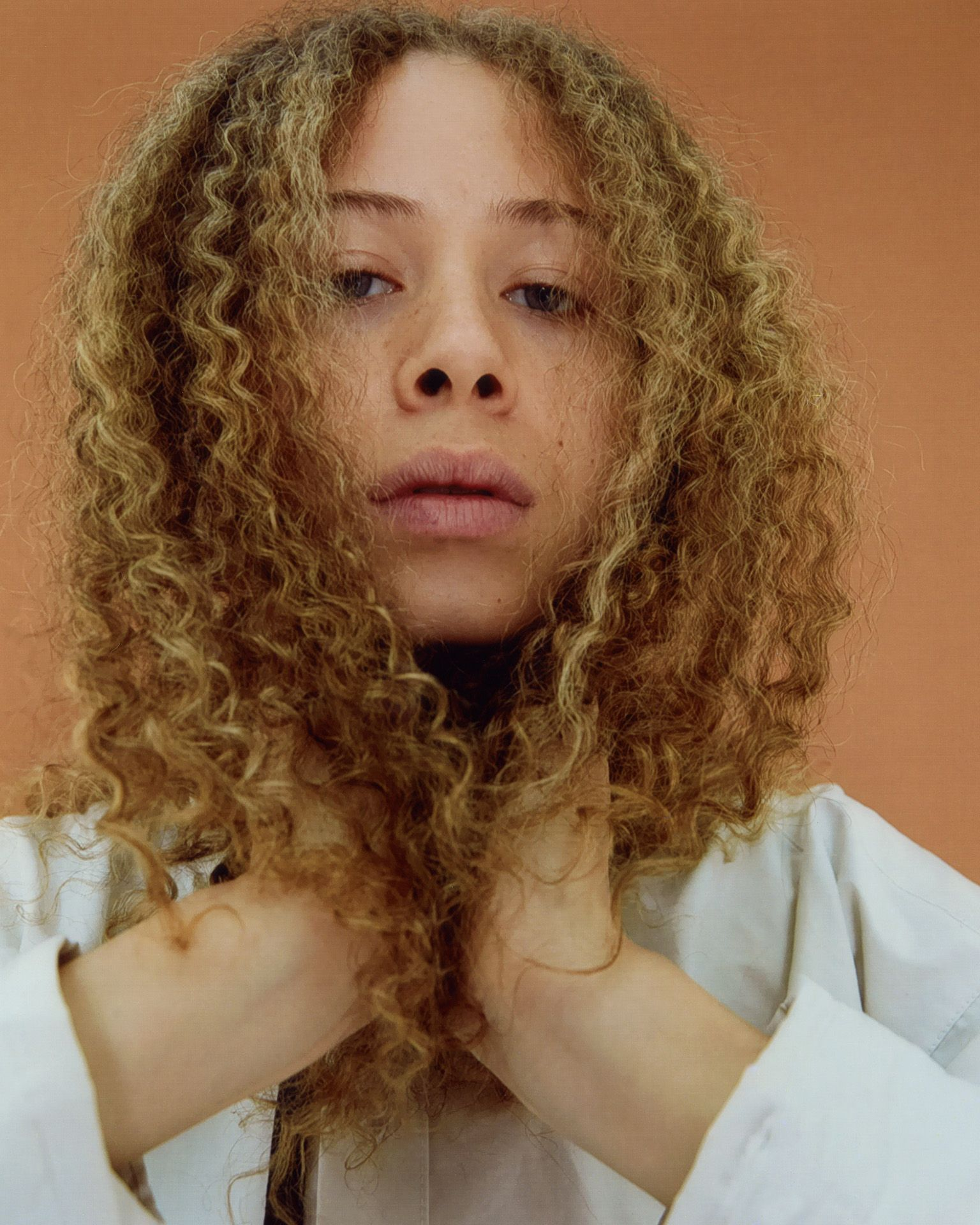 female model with curly blond hair on dark orange background by Oumayma B Tanfous for Document Journal Barragannnn casting summer spring 2020