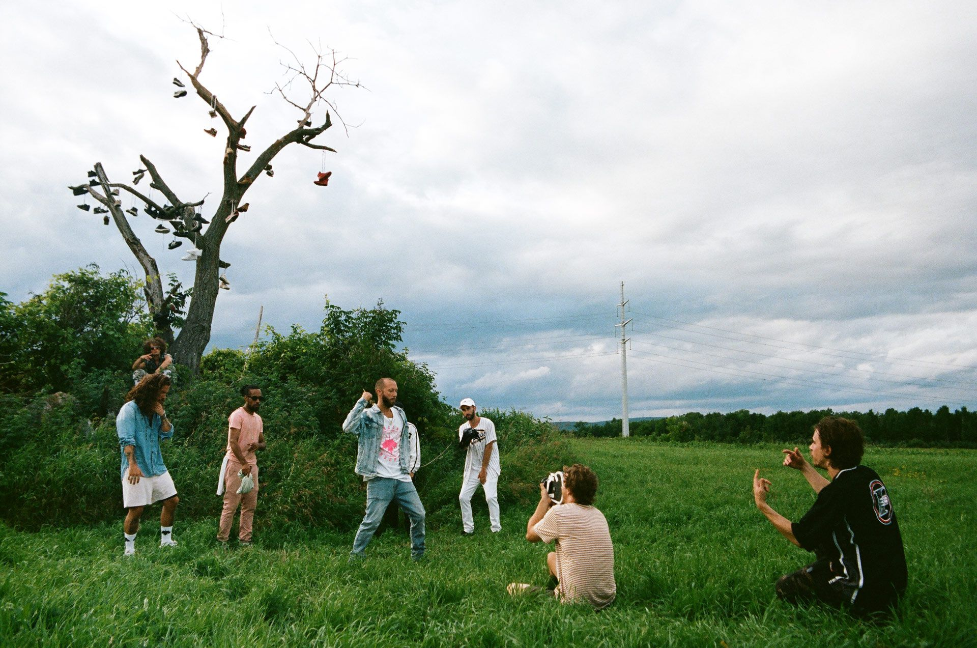 Vincent Ruel-Cote from Les Gamins crouching in field while filming Alaclair Ensemble hip hop collective music video Felix featuring rapper Souldia