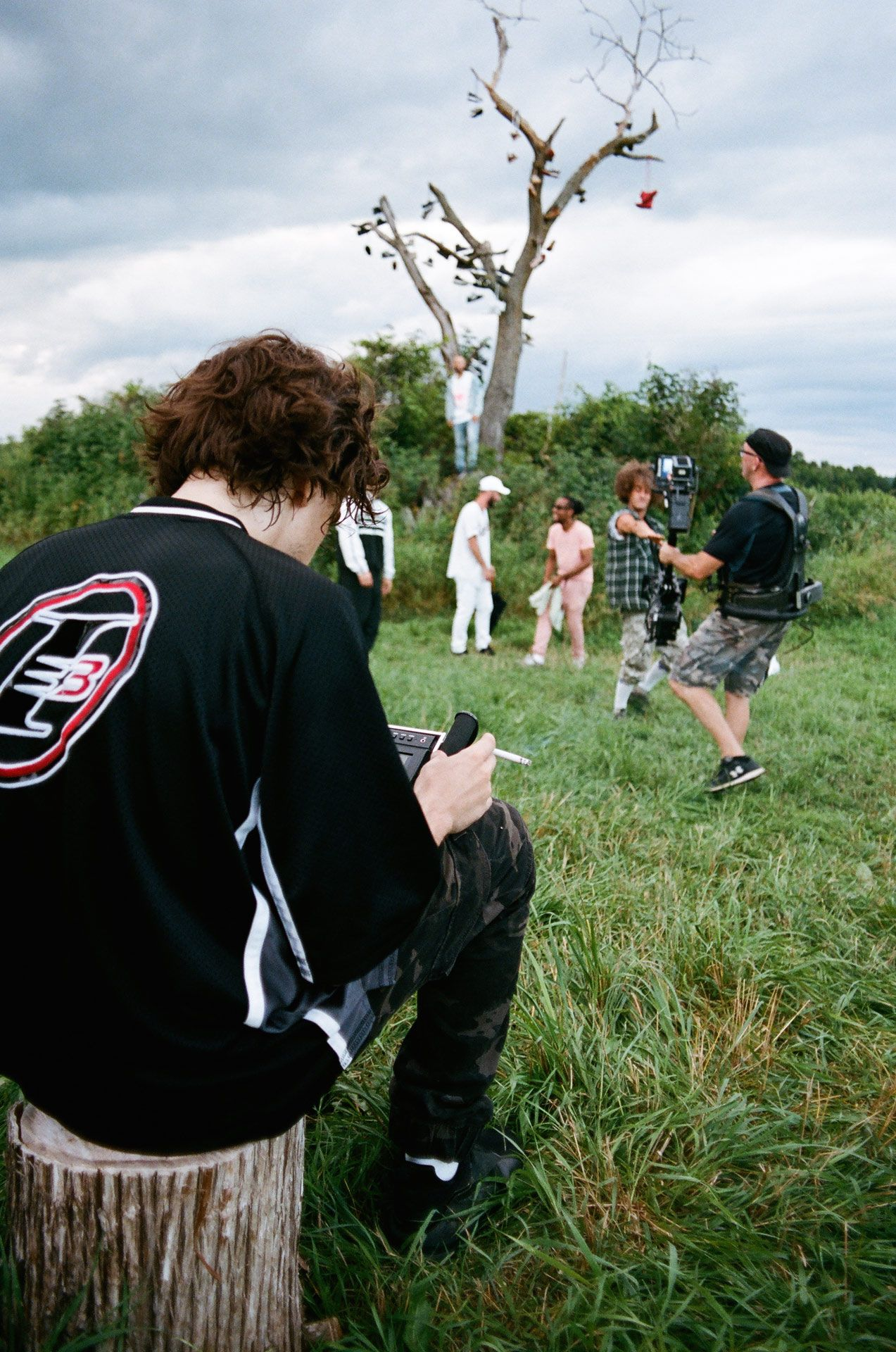 Vincent Ruel-Cote from Les Gamins sitting on wood log checking footage while filming Alaclair Ensemble hip hop collective music video Felix featuring rapper Souldia