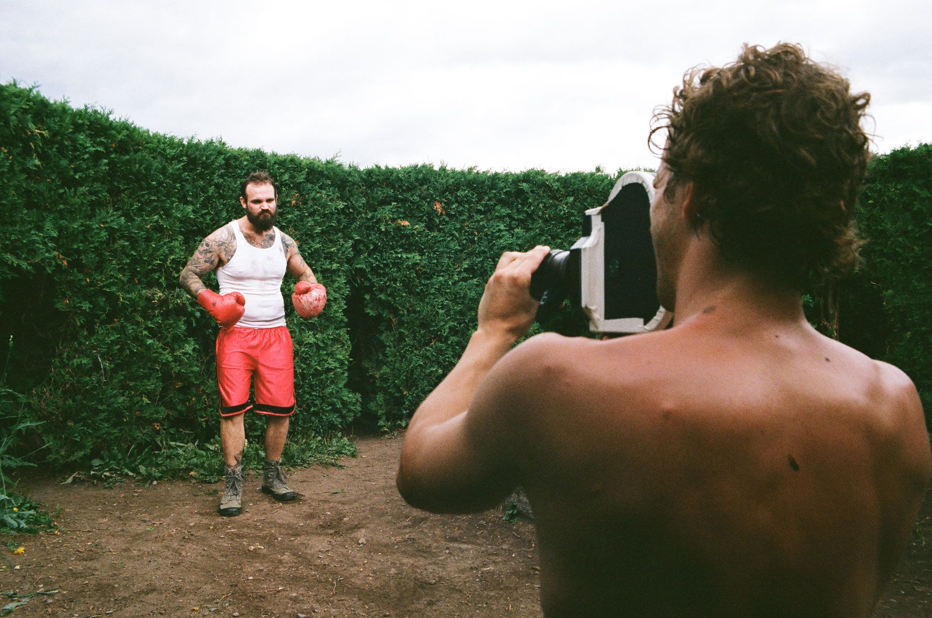 actor dressed as boxer with red gloves being filmed by a shirtless cameraman for Alaclair Ensemble hip hop collective music video Felix filmed by Les Gamins featuring rapper Souldia