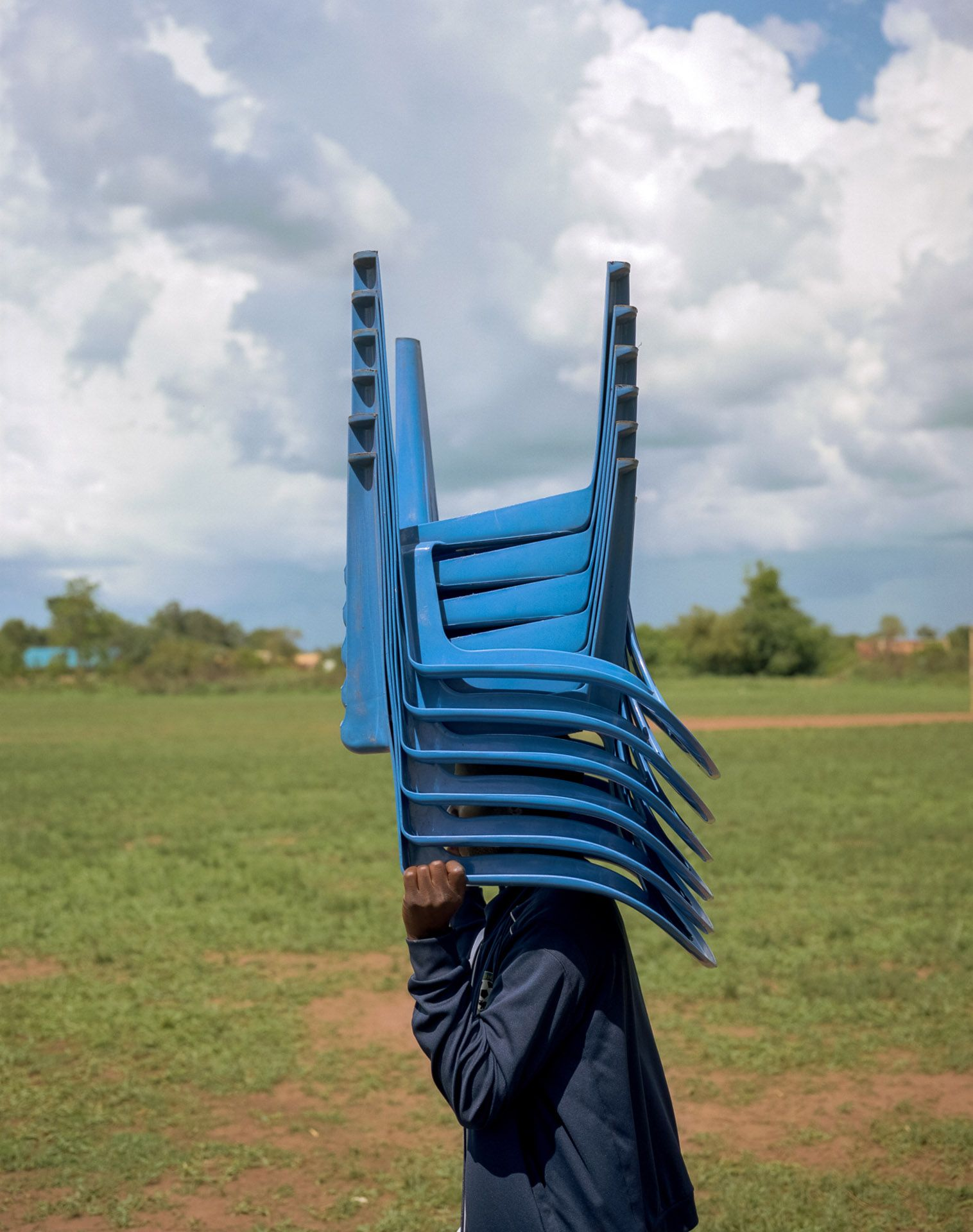 young black boy transporting a pile of blue plastic chairs upside down on his head by Alexi Hobbs in Uganda for Football for good with Sportsnet