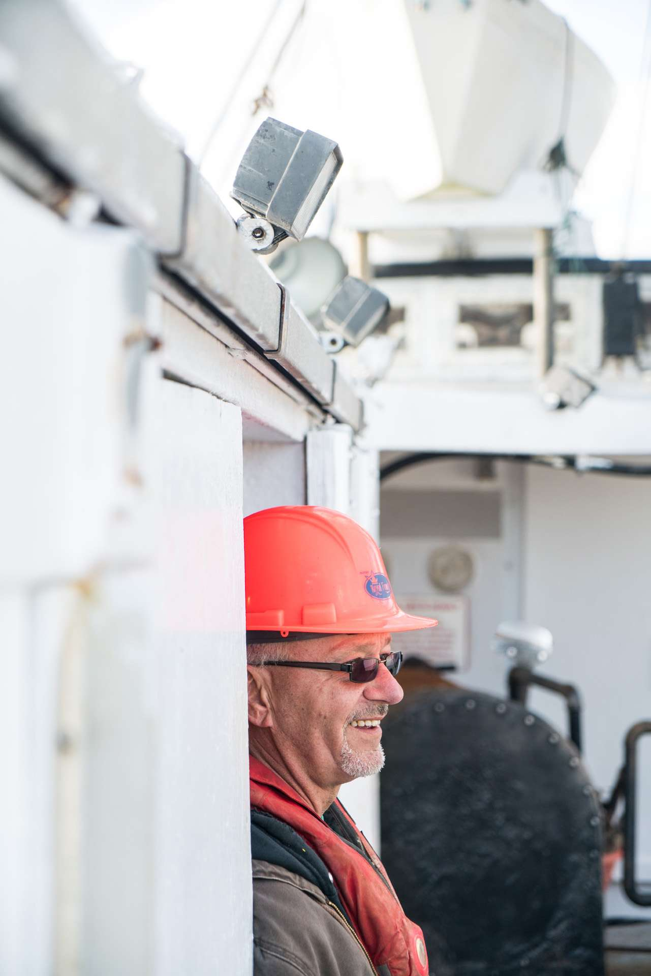 fisherman wearing red helmet and sunglasses smiling looking away by Bruno Florin for Ricardo Magazine in Bay of Fundy