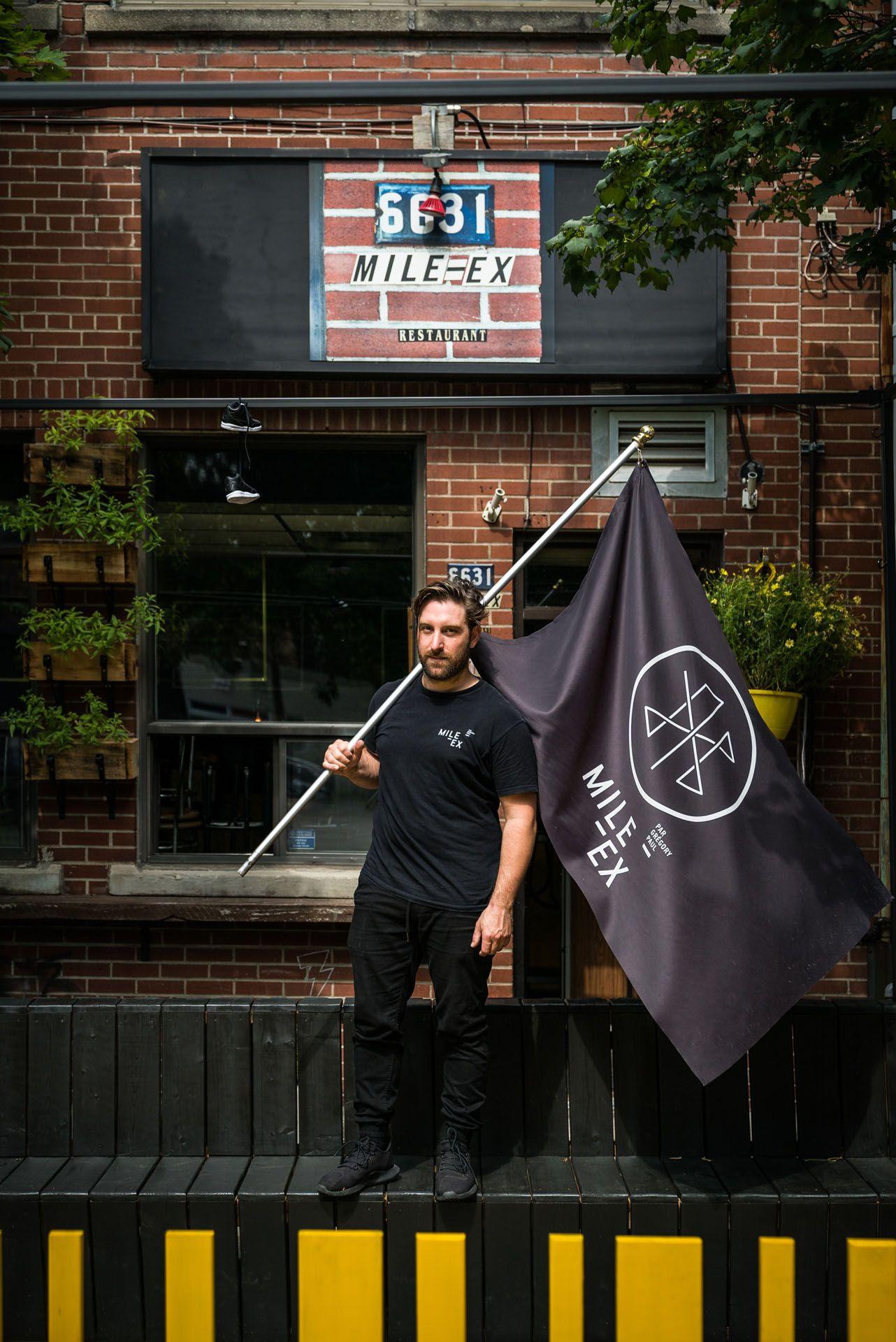 man posing on black bench dressed all in black holding huge flag owner of Mile Ex restaurant by Bruno Florin for mile ex mille vie