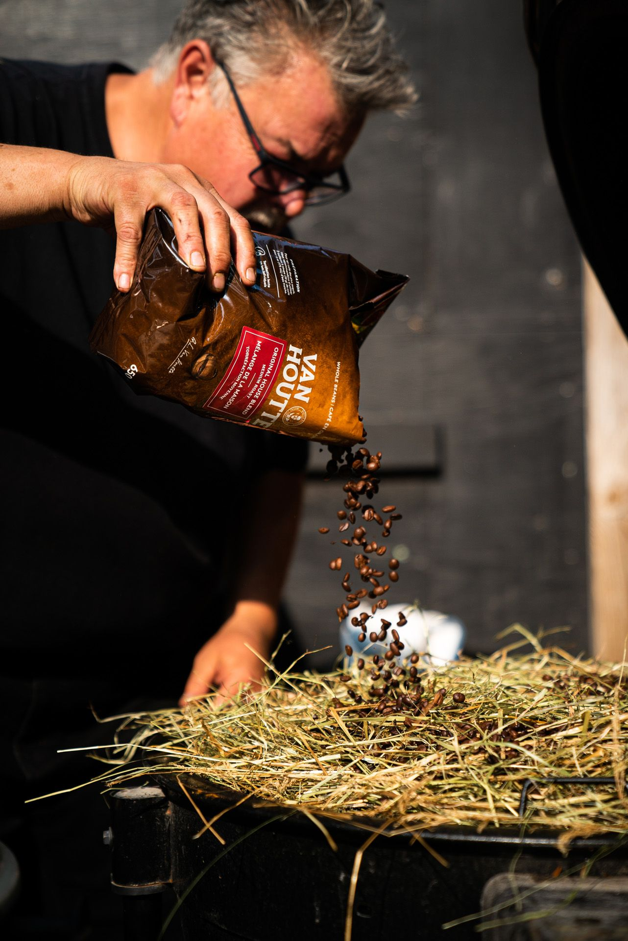 chef Ted Reader pouring roasted coffee beans on cooking hay by Bruno Florin for Van Houtte 100th anniversary