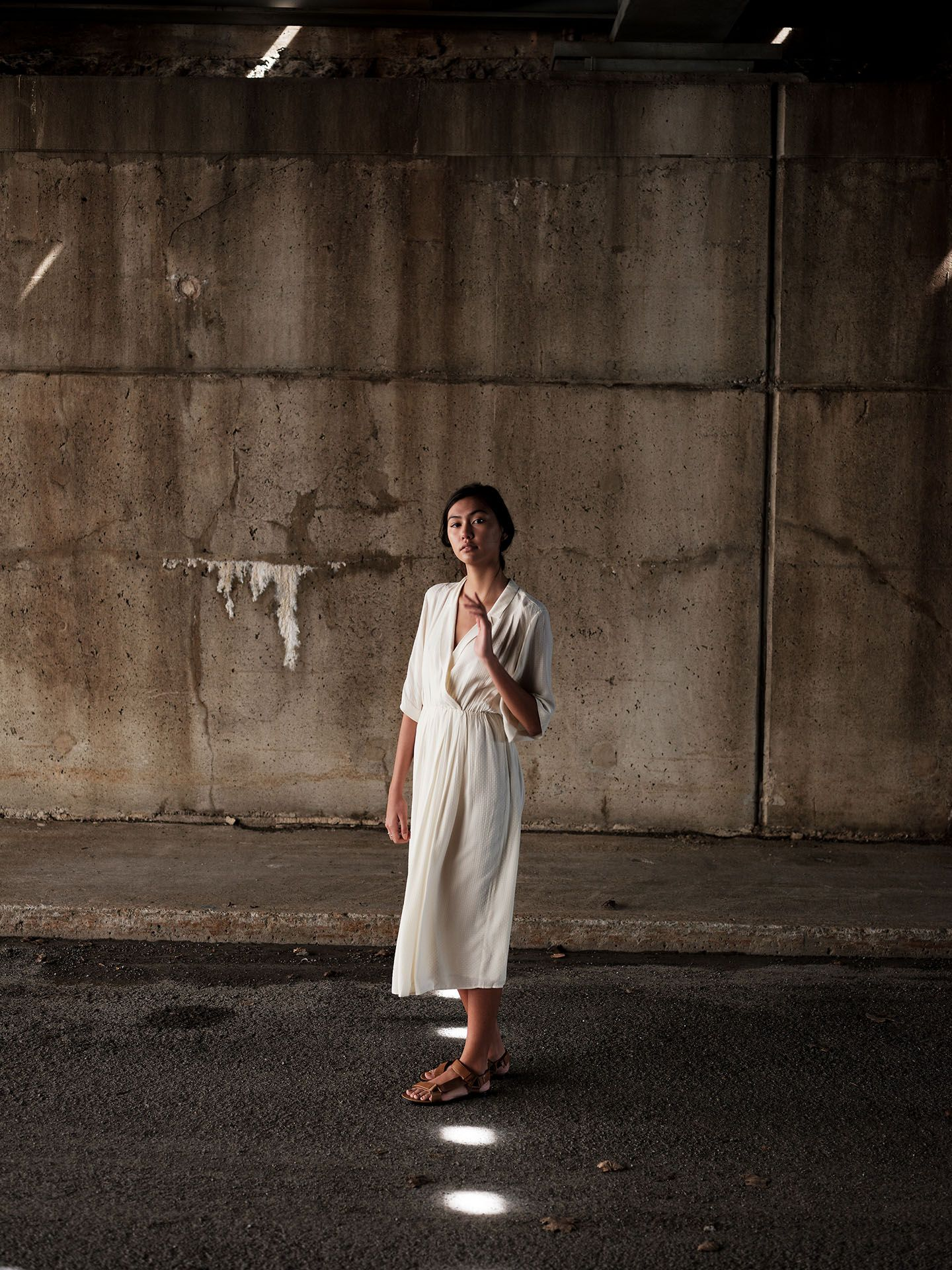 woman of colour modelling under concrete bridge walking on white painted dots on the ground wearing white flowy dress looking at camera softly by Guillaume Simoneau for Swell and Ginger SS19
