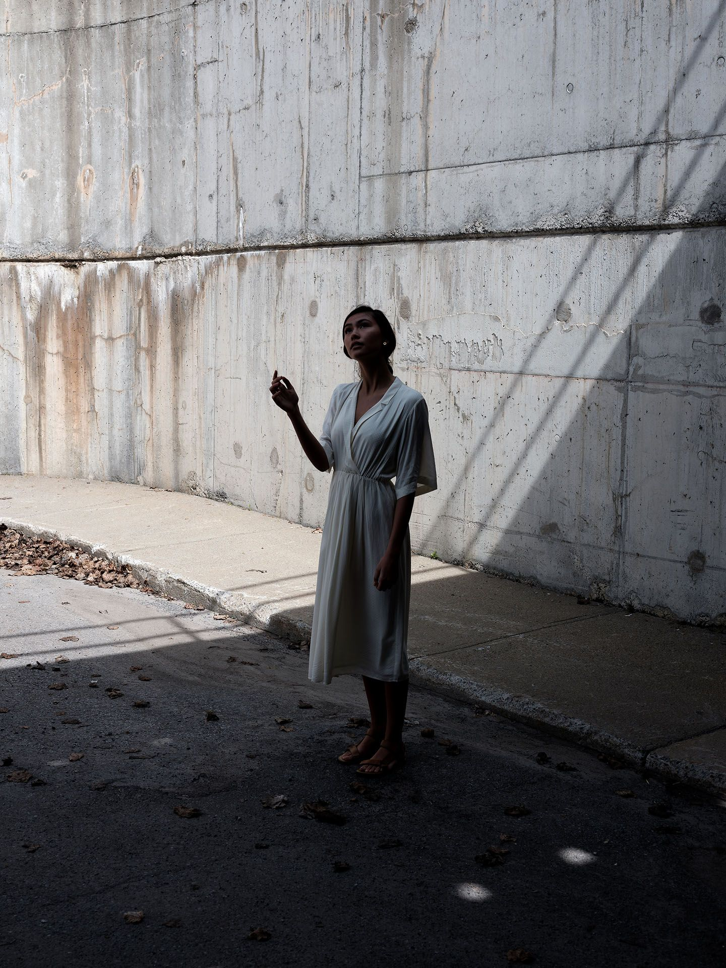 woman of colour model Anais under concrete bridge wearing white flowy dress standing in the shadows with her hand up looking up by Guillaume Simoneau for Swell and Ginger SS19