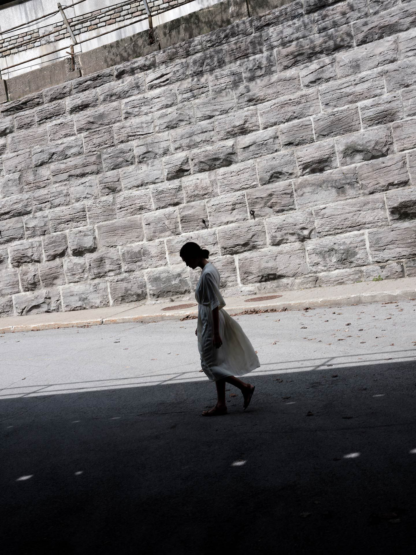 woman of colour model Anais under concrete bridge wearing white flowing in the wind dress walking in the shadows looking down by Guillaume Simoneau for Swell and Ginger SS19