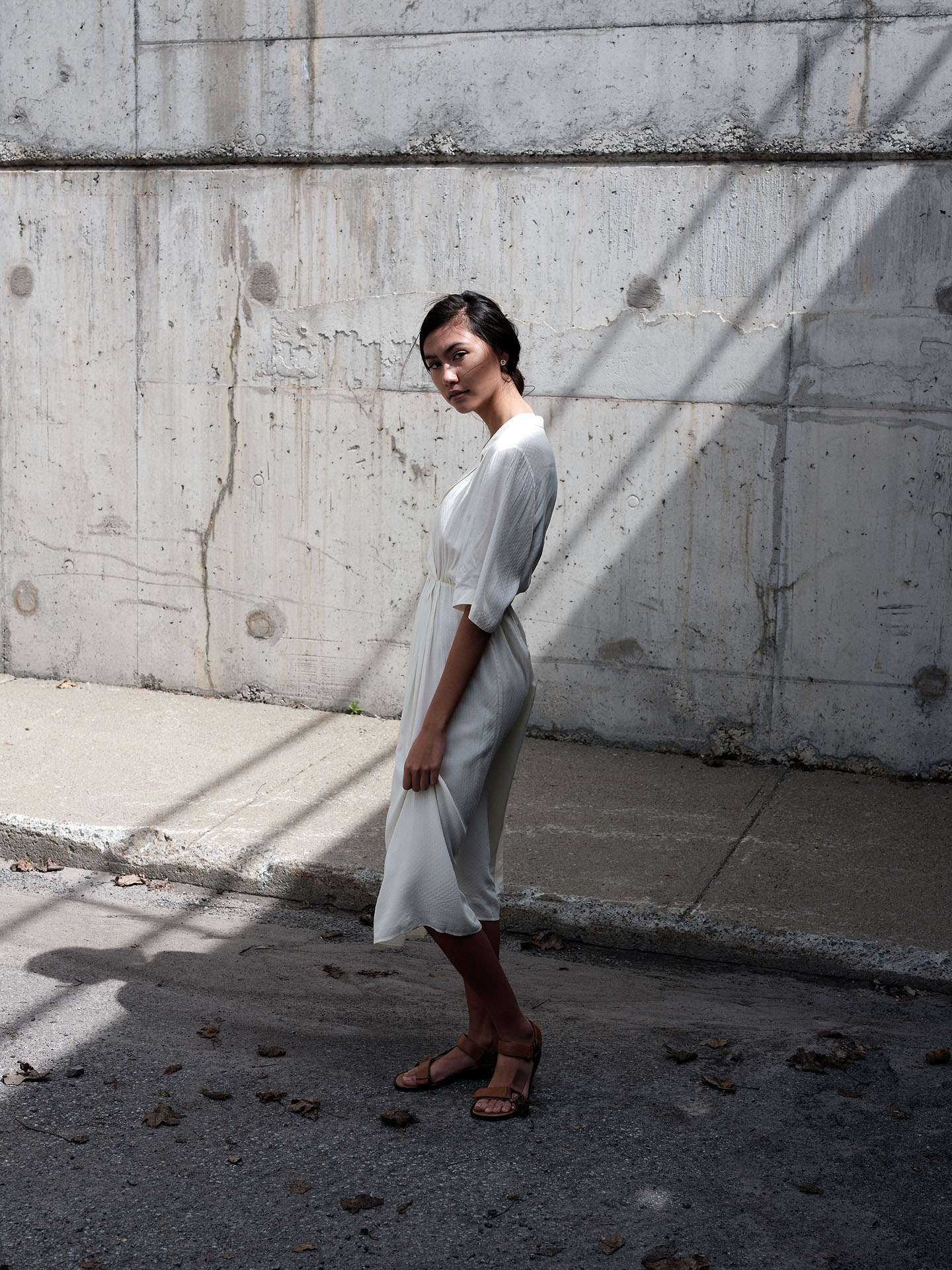 woman of colour modelling under concrete bridge wearing white flowy dress looking at camera softly by Guillaume Simoneau for Swell and Ginger SS19