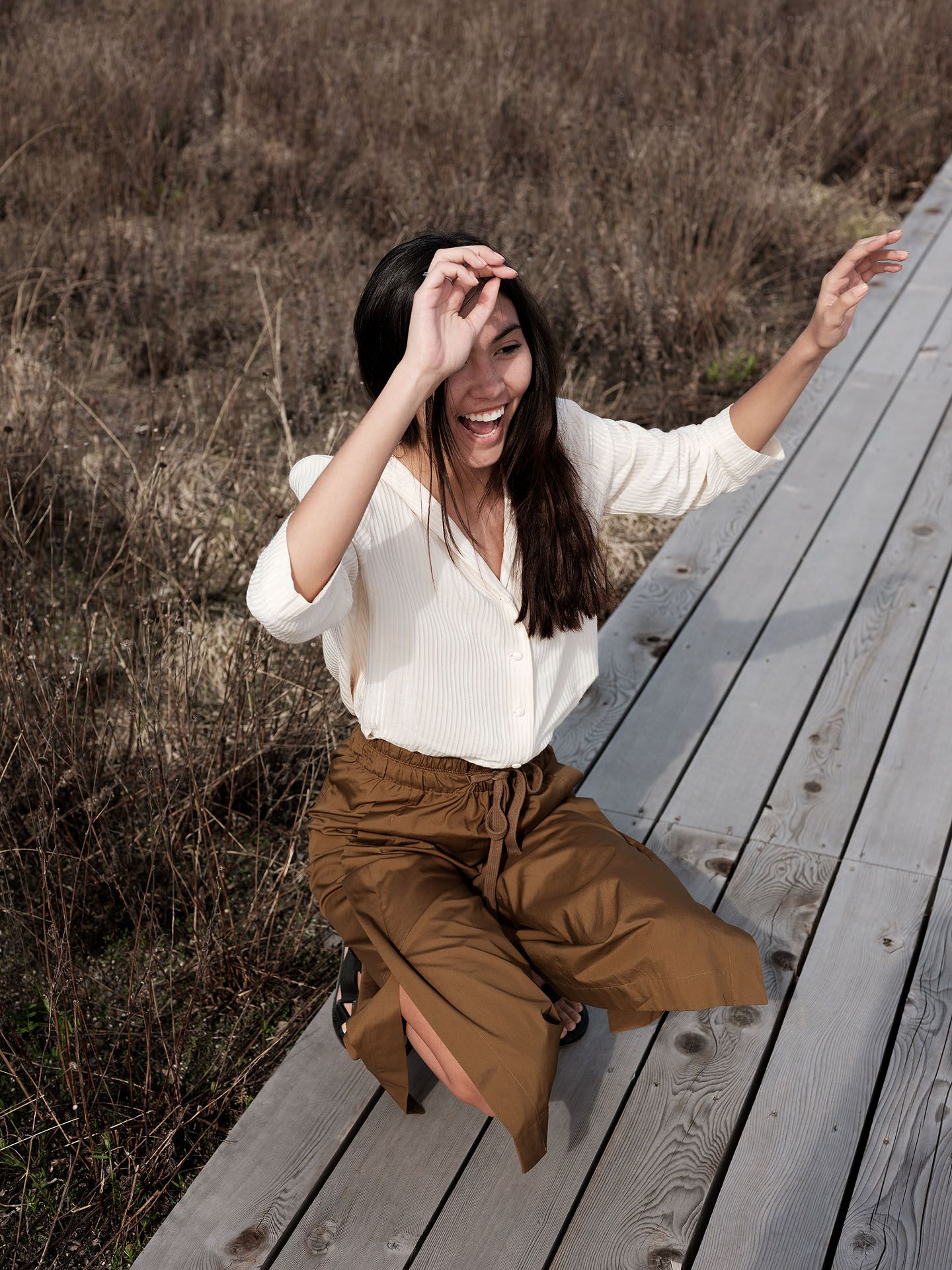 woman of colour model Anaïs crouching on wood-planks path wearing dark camel pants and soft white blouse laughing while trying to stay upright for the spring-summer collection of Swell & Ginger by Guillaume Simoneau