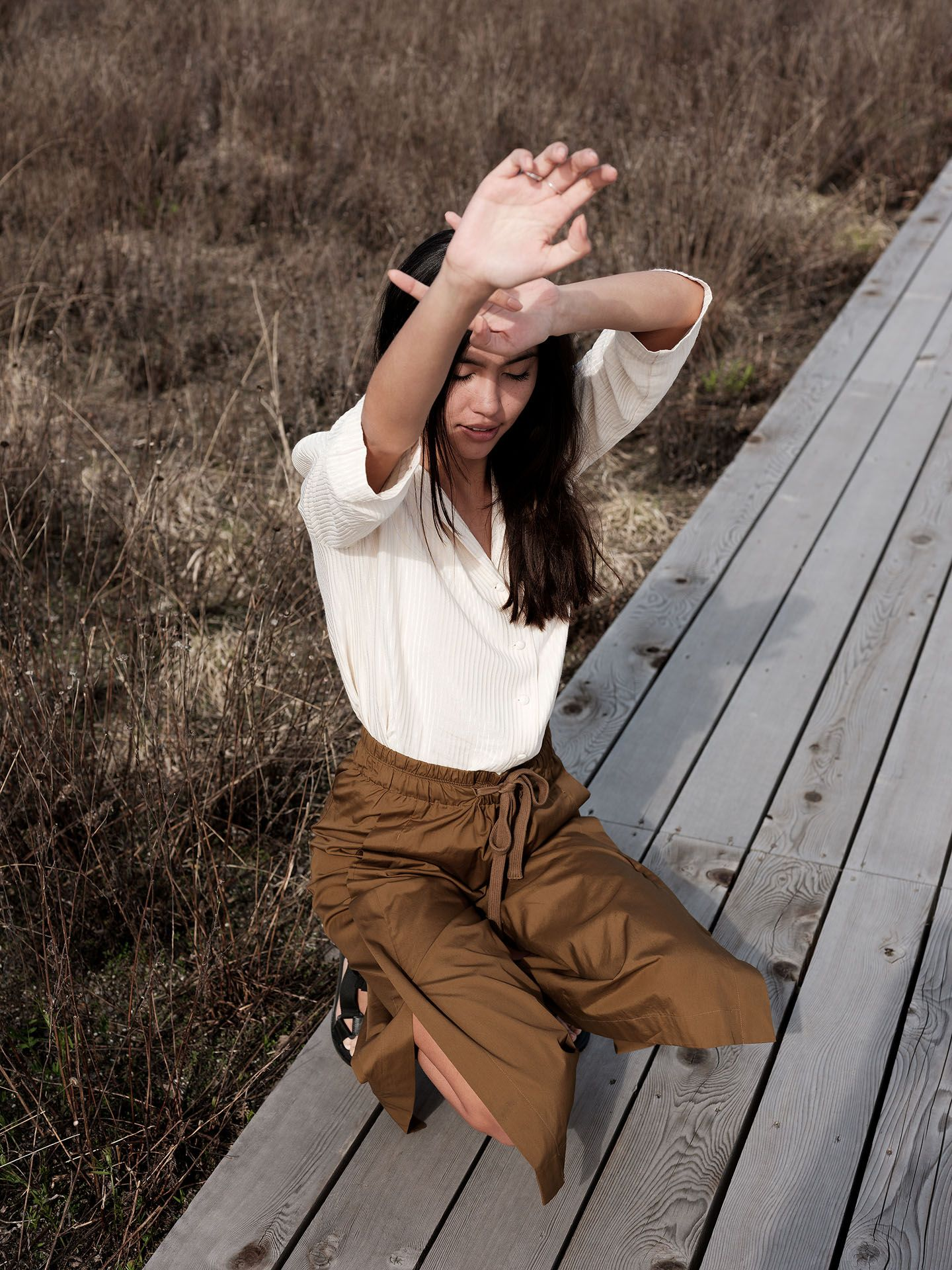 woman of colour model Anaïs crouching on wood-planks path wearing dark camel pants and soft white blouse stretching one of her arms up with her eyes closed for the spring-summer collection of Swell & Ginger by Guillaume Simoneau