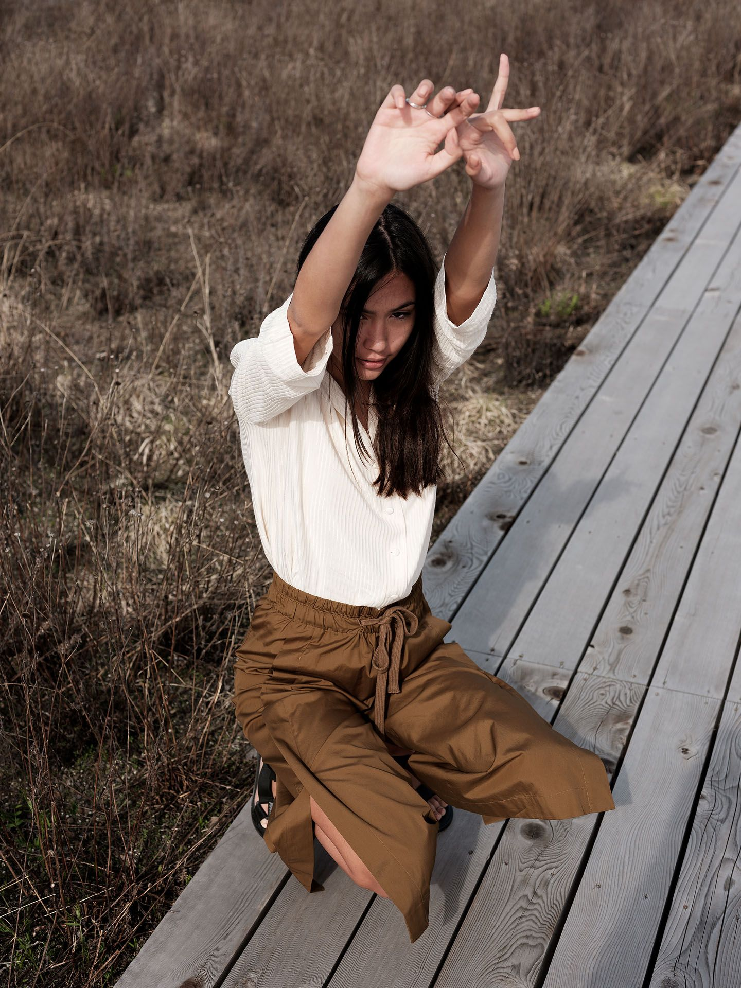 woman of colour model Anaïs crouching on wood-planks path wearing dark camel pants and soft white blouse stretching her arms up for the spring-summer collection of Swell & Ginger by Guillaume Simoneau