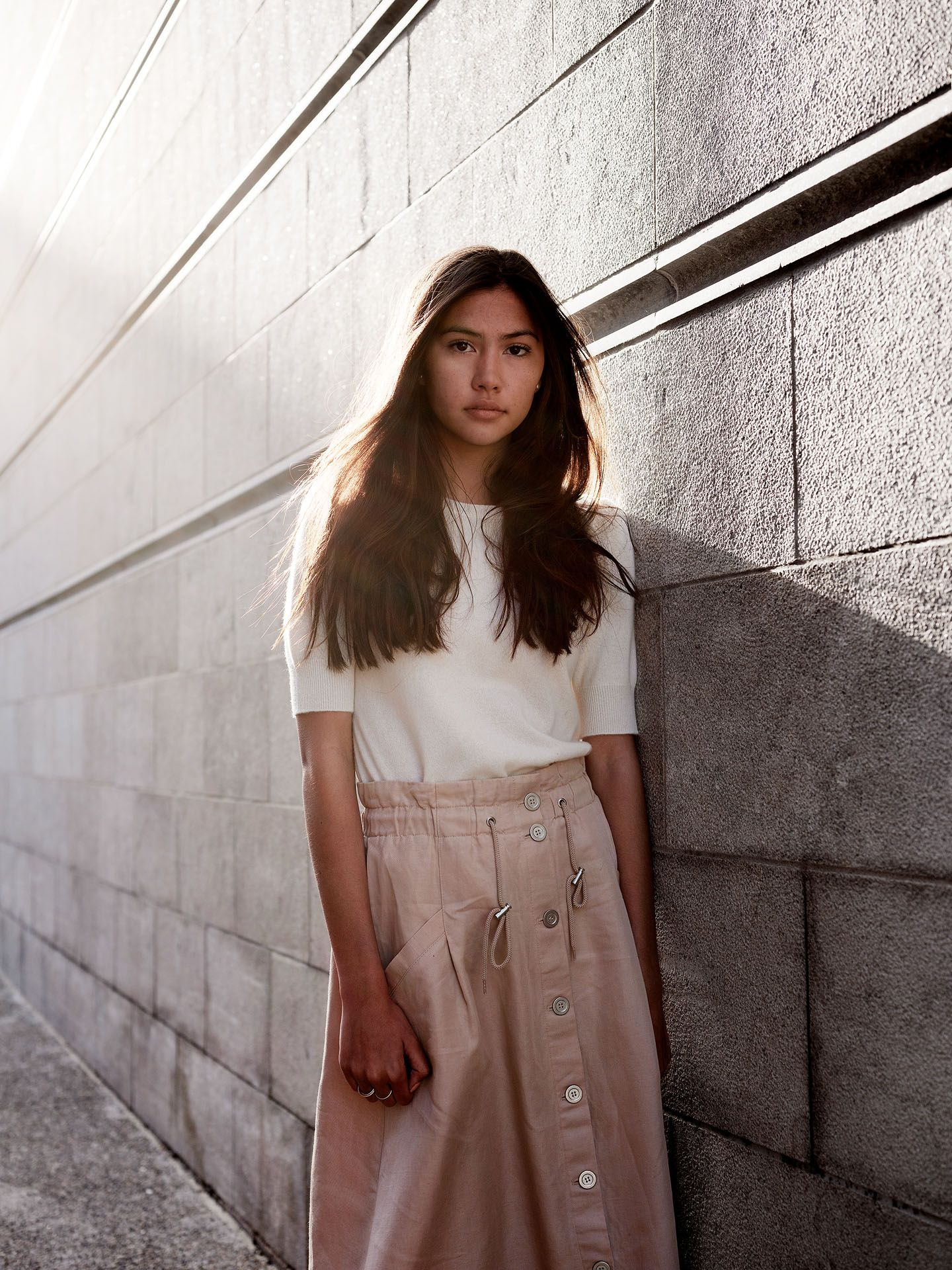 woman of colour model Anaïs posing against concrete wall with the sun on her back looking at camera wearing soft white shirt and pink skirt for the spring-summer collection of Swell & Ginger by Guillaume Simoneau
