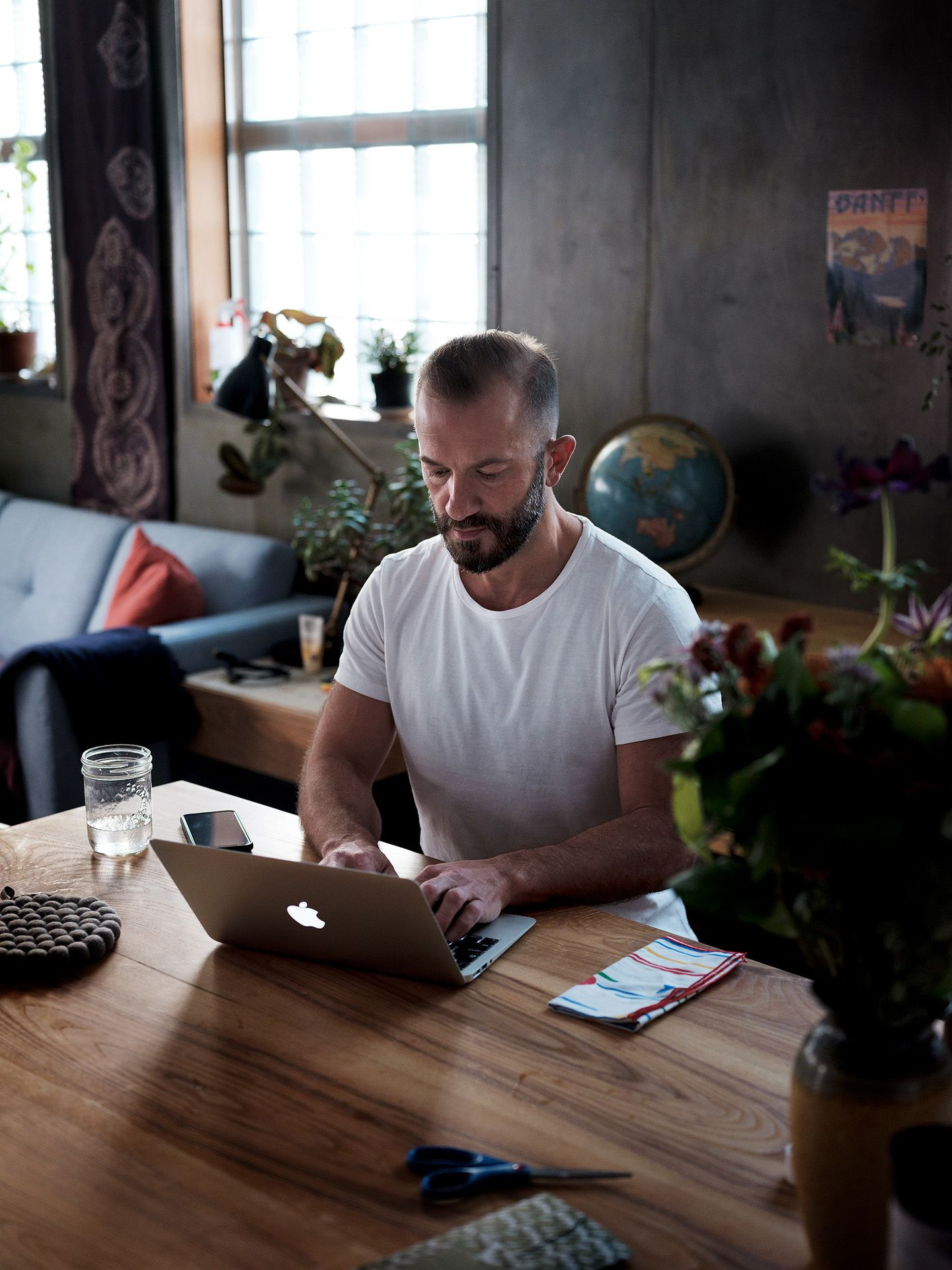 saxophonist and composer Colin Stetson sitting at table working on his macbook wearing white shirt photographed by Guillaume Simoneau