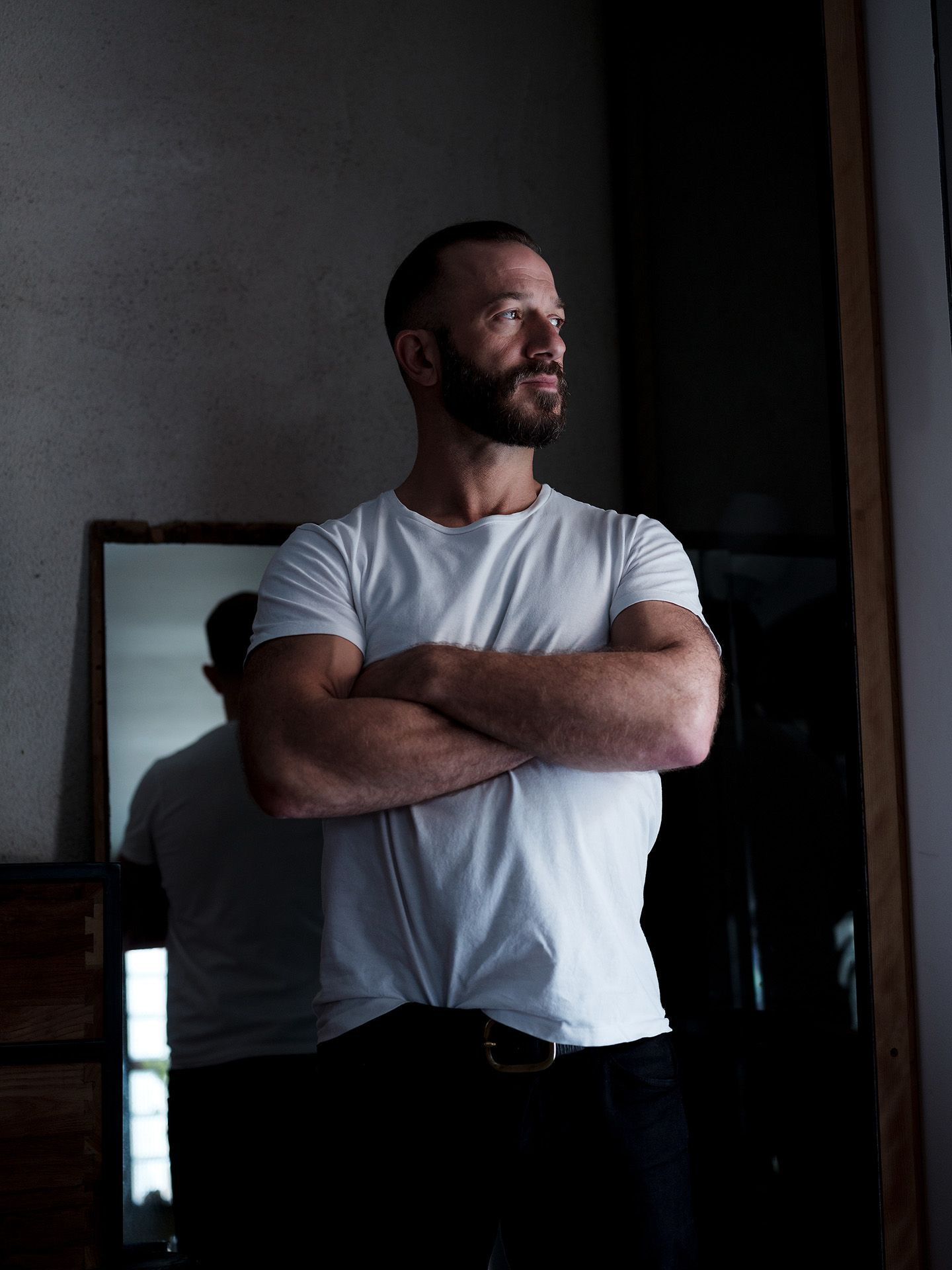 saxophonist and composer Colin Stetson wearing white shirt posing next to a window with his arms crossed looking out to the outside photographed by Guillaume Simoneau