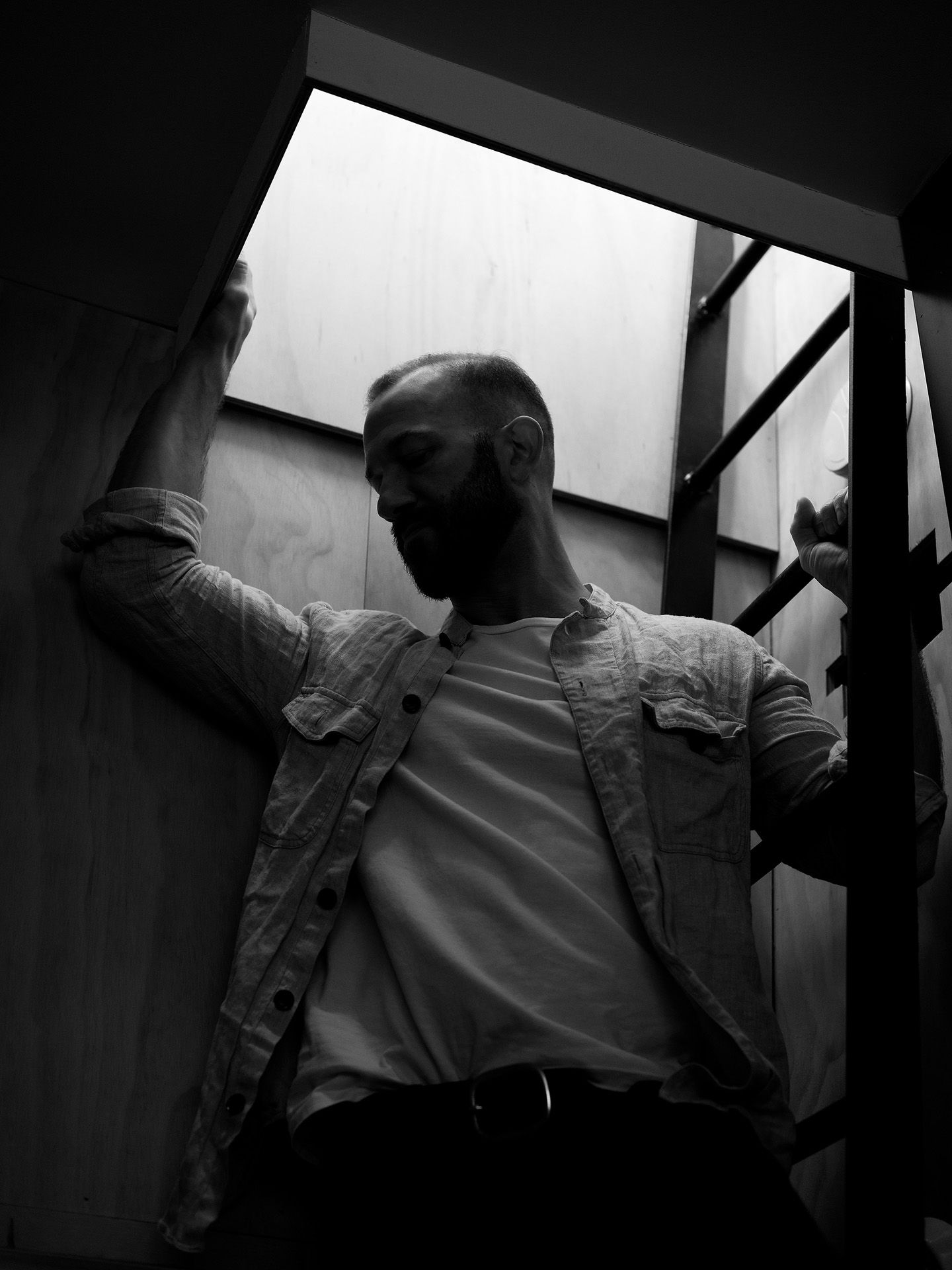 saxophonist and composer Colin Stetson holding onto a ladder light coming from above picture in black and white photographed by Guillaume Simoneau