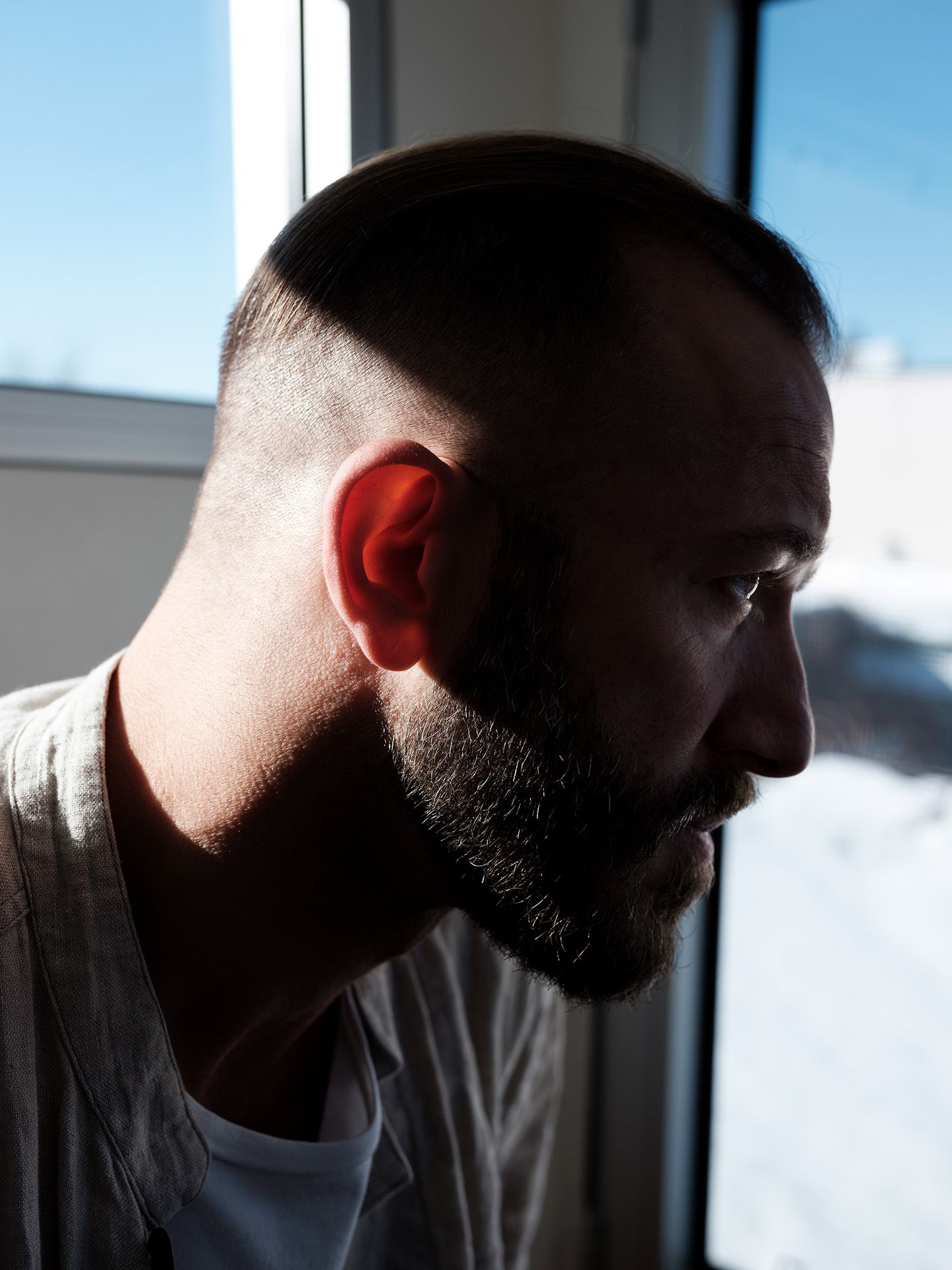 close up of profile of saxophonist and composer Colin Stetson with light on the back of his head photographed by Guillaume Simoneau