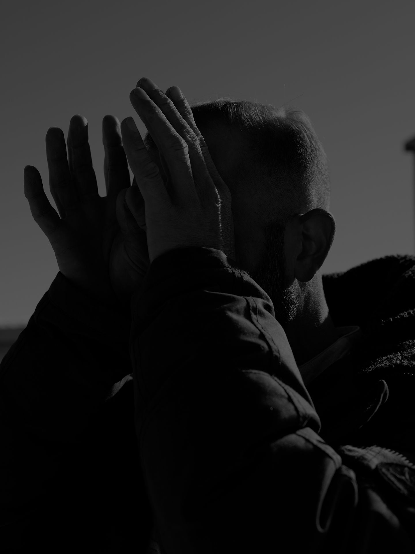 close up of saxophonist and composer Colin Stetson with light on the back of his head back of his hands on his face picture in black and white photographed by Guillaume Simoneau