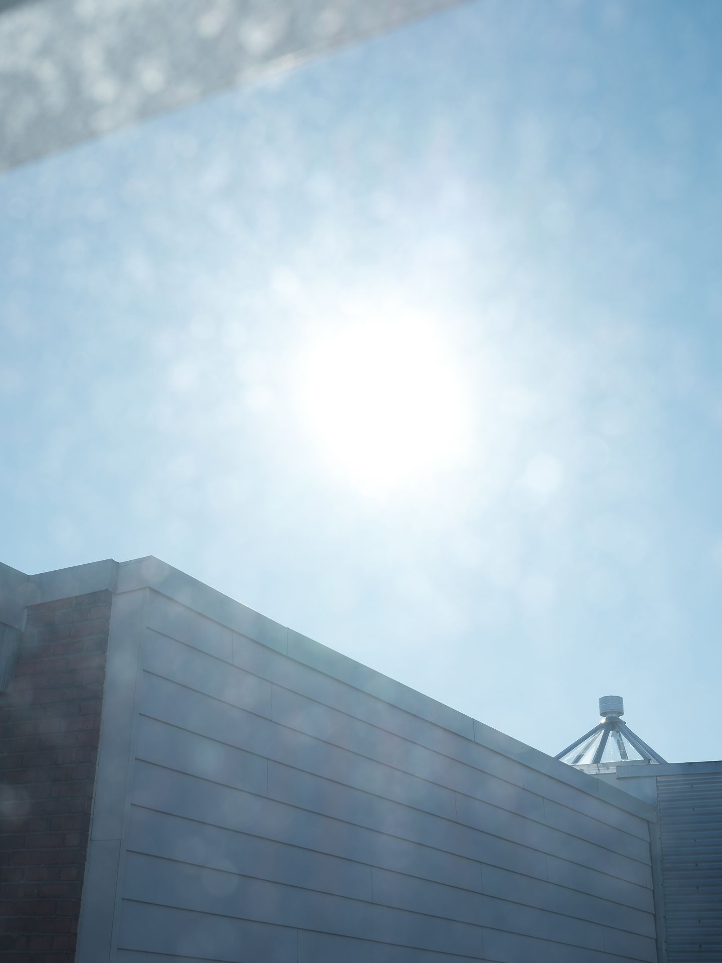 building through a window with sun flare photographed by Guillaume Simoneau