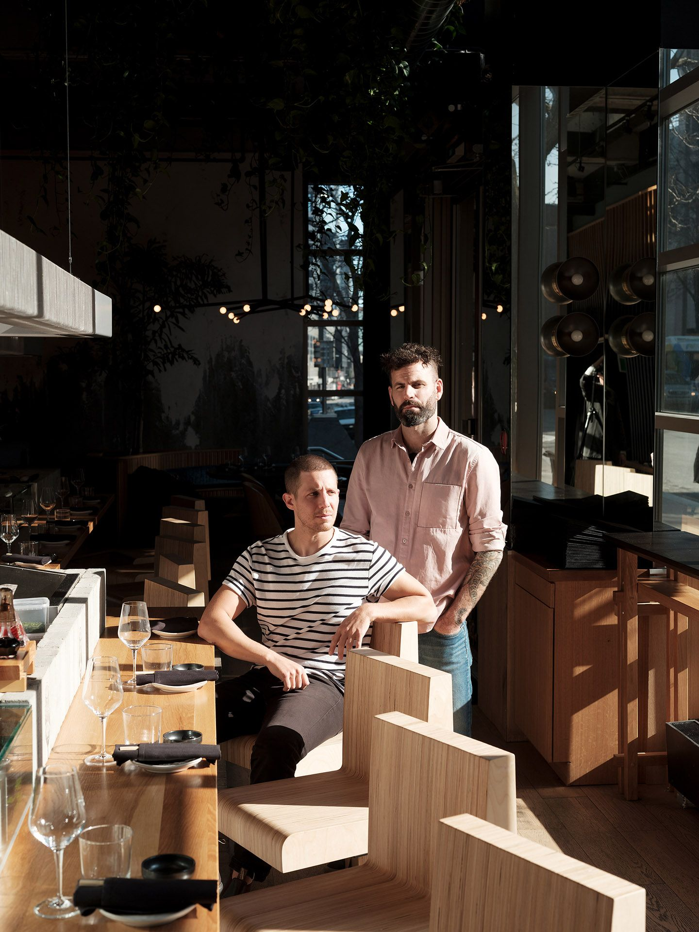 owners two men next to bar one sitting leaning on the counter the second standing behind him both face in the sun looking serious faces in the sun by Guillaume Simoneau at MRDK for NUVO