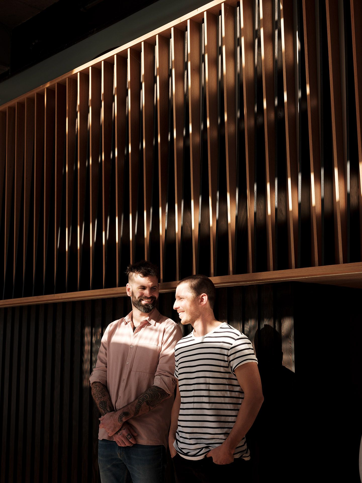 owners two men posing next to wood wall laughing with face in the sun looking casual by Guillaume Simoneau at MRDK for NUVO