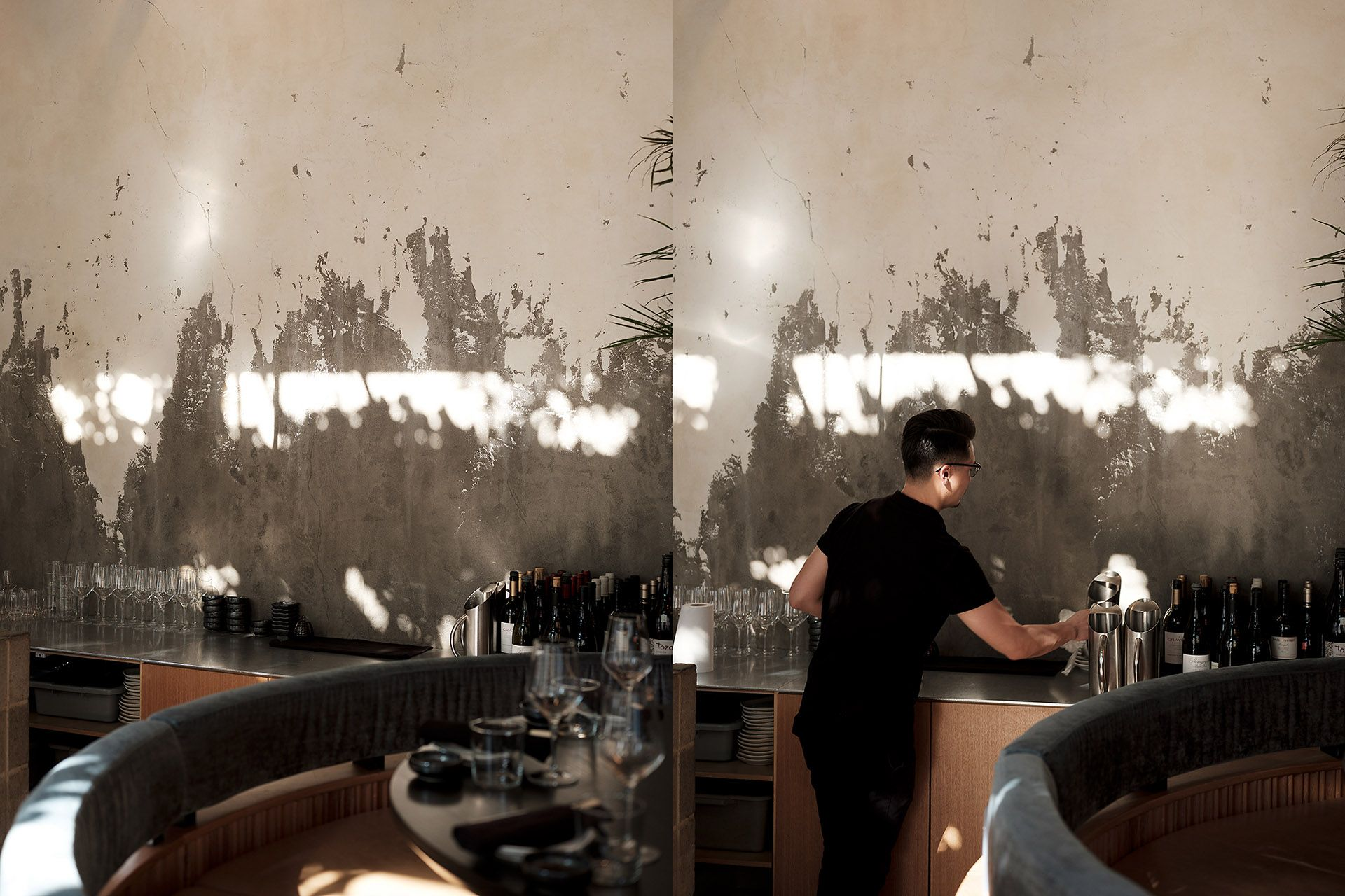 plating area of restaurant with clean glasses water pitchers and wine bottles with ray of sunlight on the wall and waiter coming to get a pitcher by Guillaume Simoneau at MRDK for NUVO