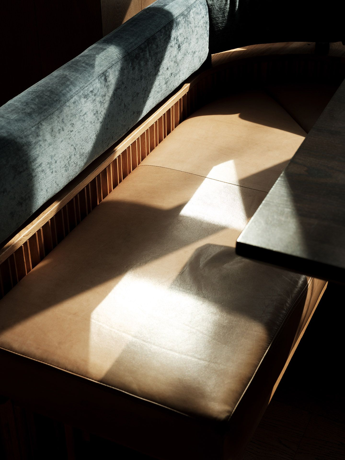 booth bench with ray on sun on the caramel leather seat and black table by Guillaume Simoneau at MRDK for NUVO