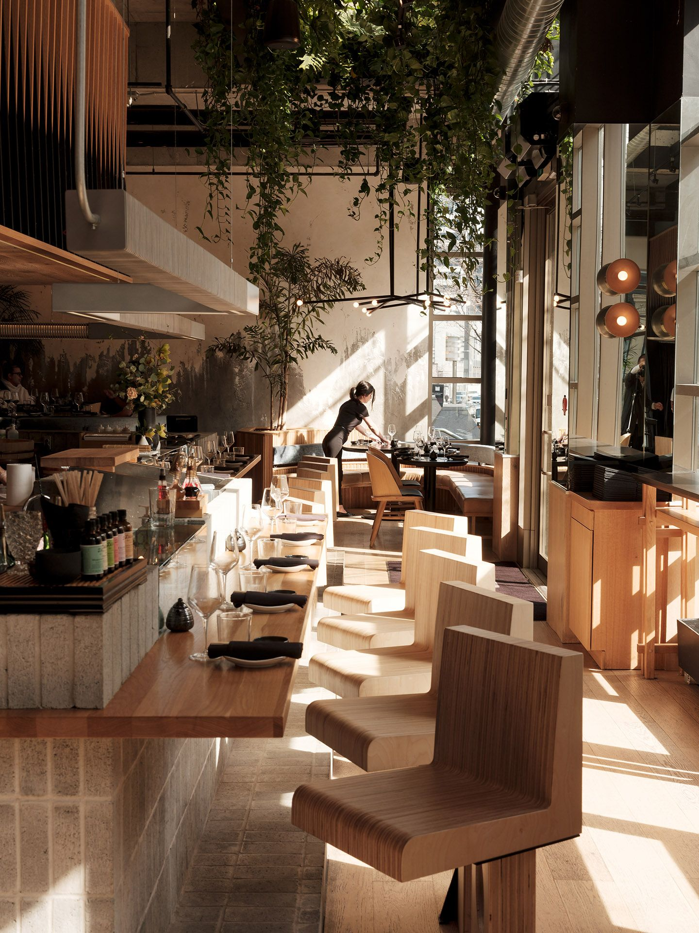 interior of high-en cafe with waitress setting up tables early in the morning by Guillaume Simoneau at MRDK for NUVO