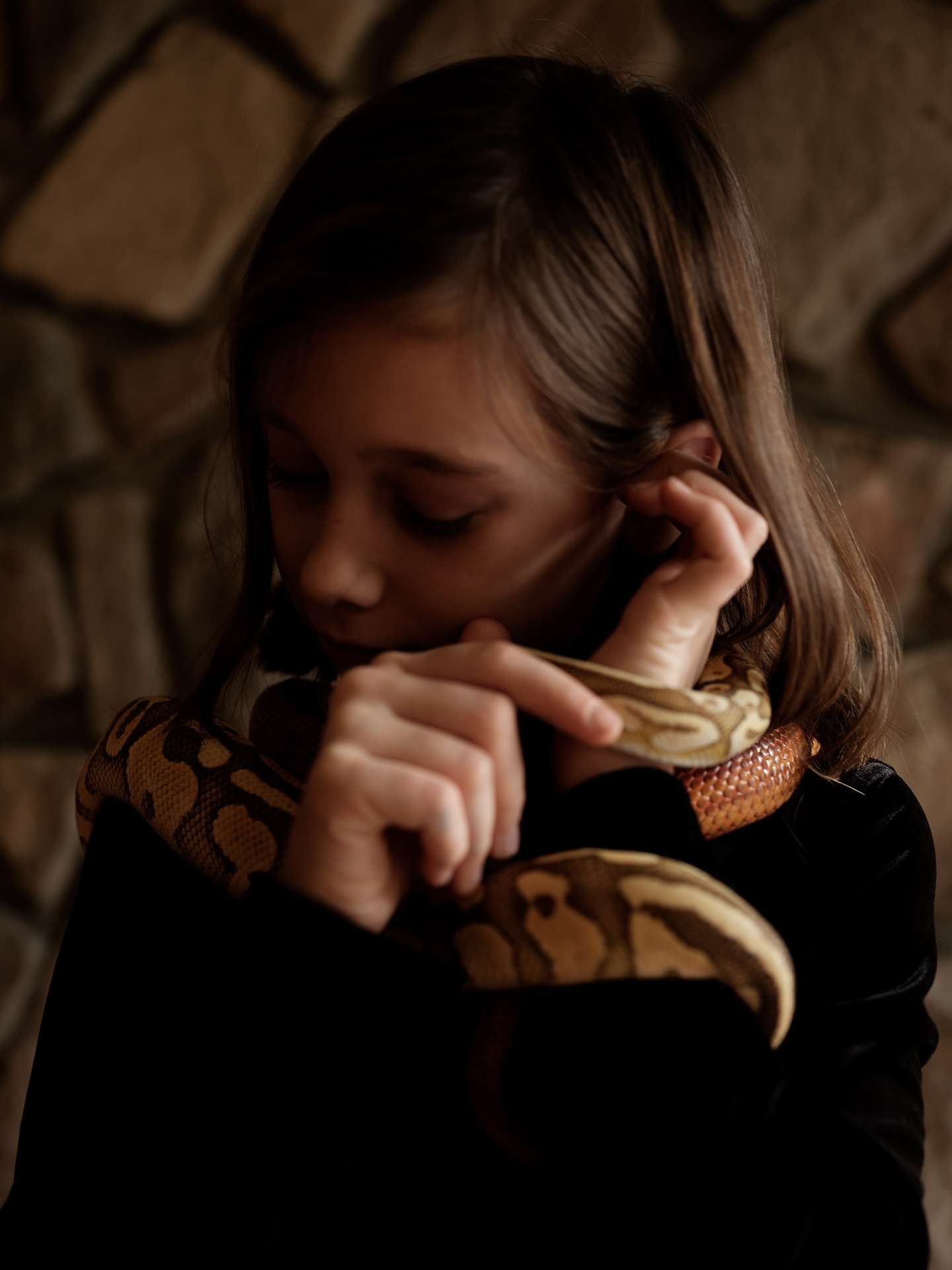 young girl brown hair holding and playing with snake by Guillaume Simoneau