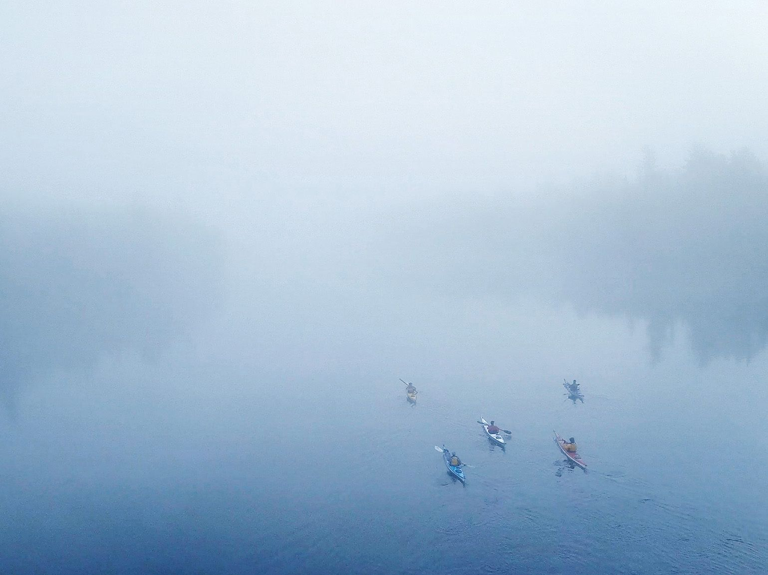 group of canoes paddling in river being engulfed in fog by Guillaume Simoneau in Abitibi