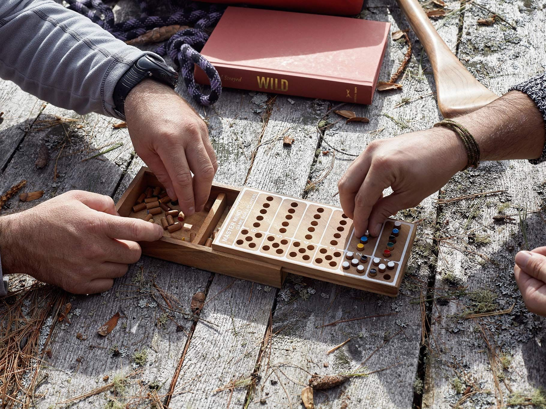 hands of two men playing a game of wooden mastermind on picnic table covered in pine cones and leaves by Guillaume Simoneau in Abitibi