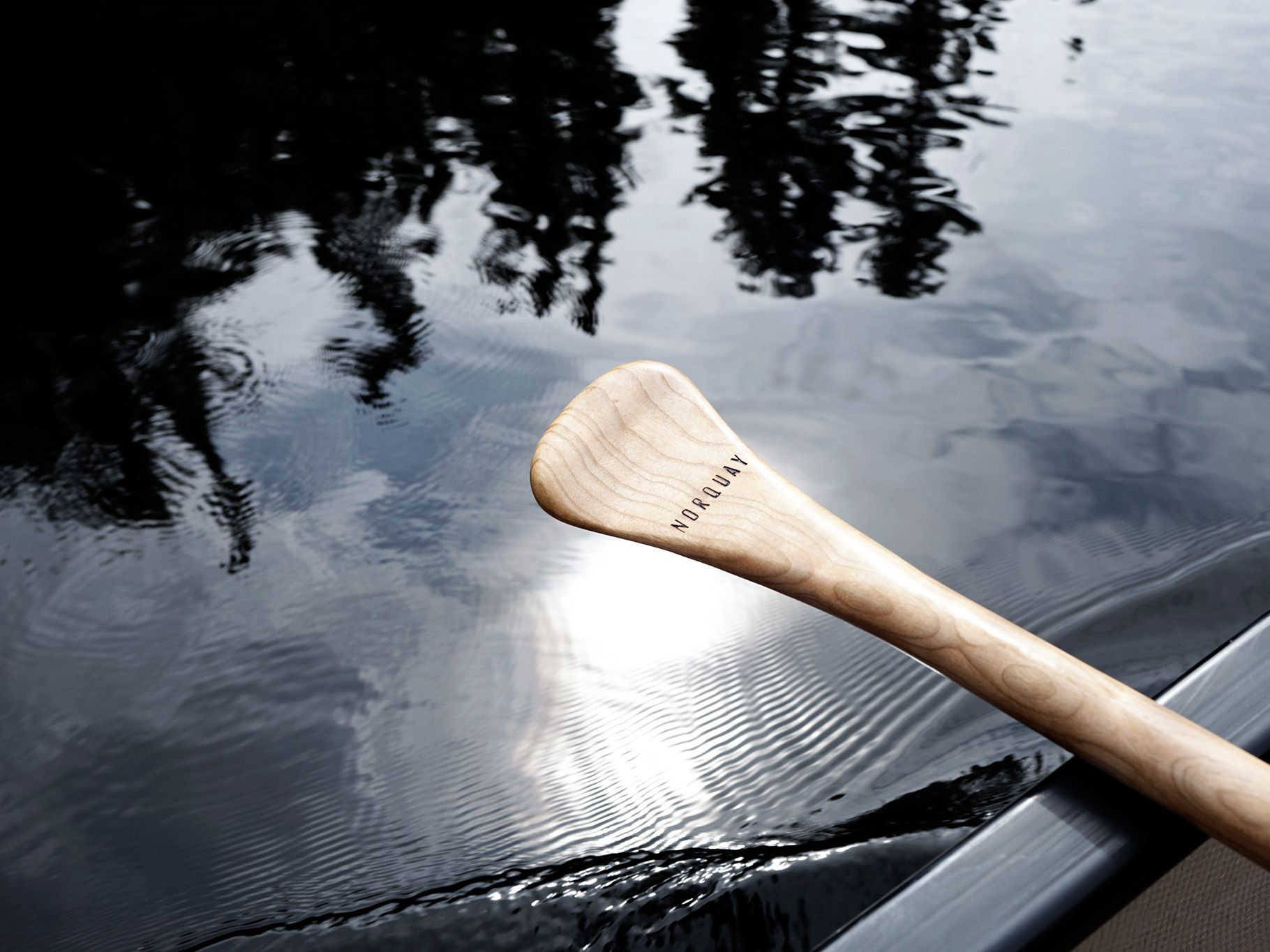 handle of wooden paddle in canoe over river by Guillaume Simoneau in Abitibi