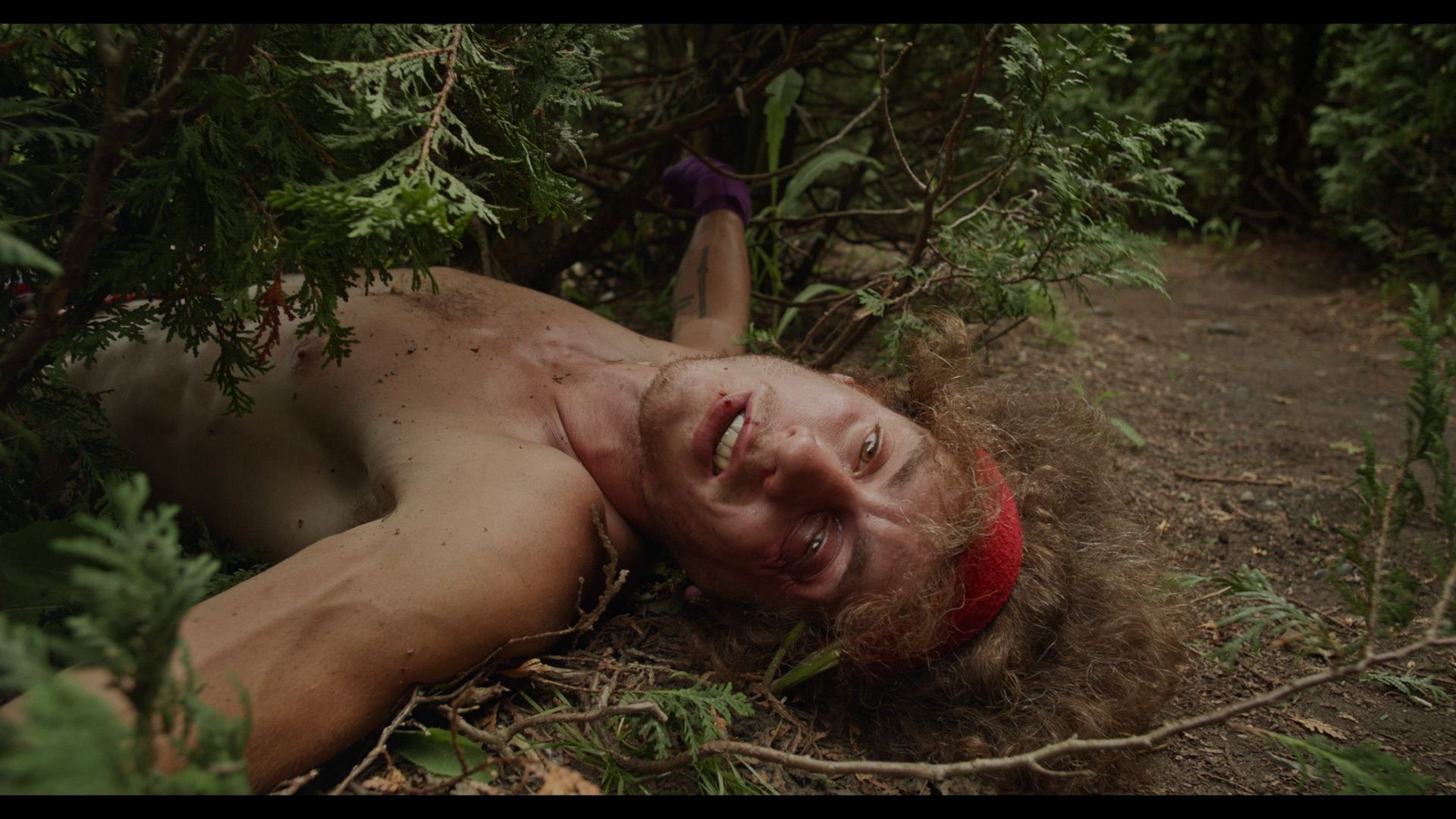 actor beaten up on the ground half his body under a bush looking directly at camera for Alaclair Ensemble hip hop collective music video Felix filmed by Les Gamins featuring Souldia