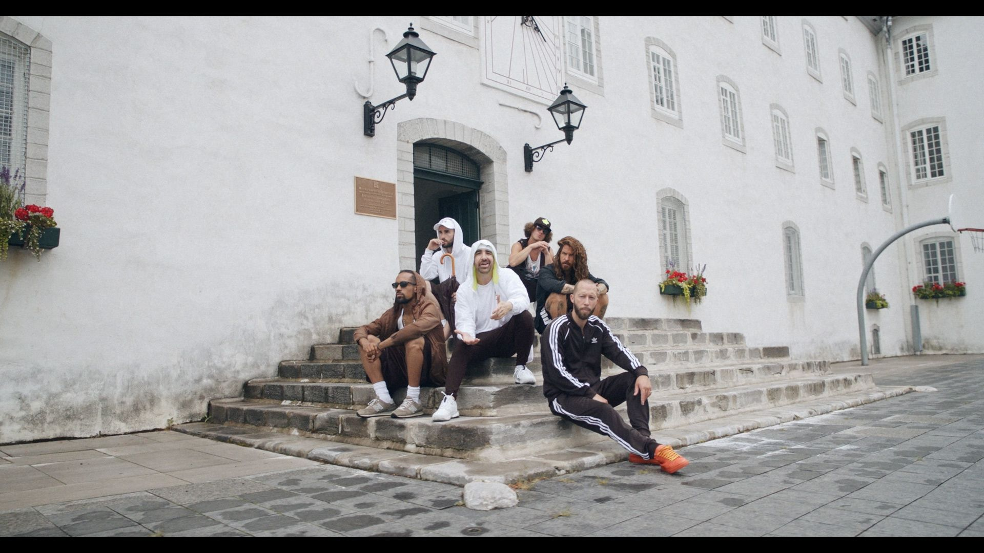 Alaclair Ensemble hip hop collective members sitting in stone stairs of building looking at camera for music video Felix filmed by Les Gamins featuring rapper Souldia