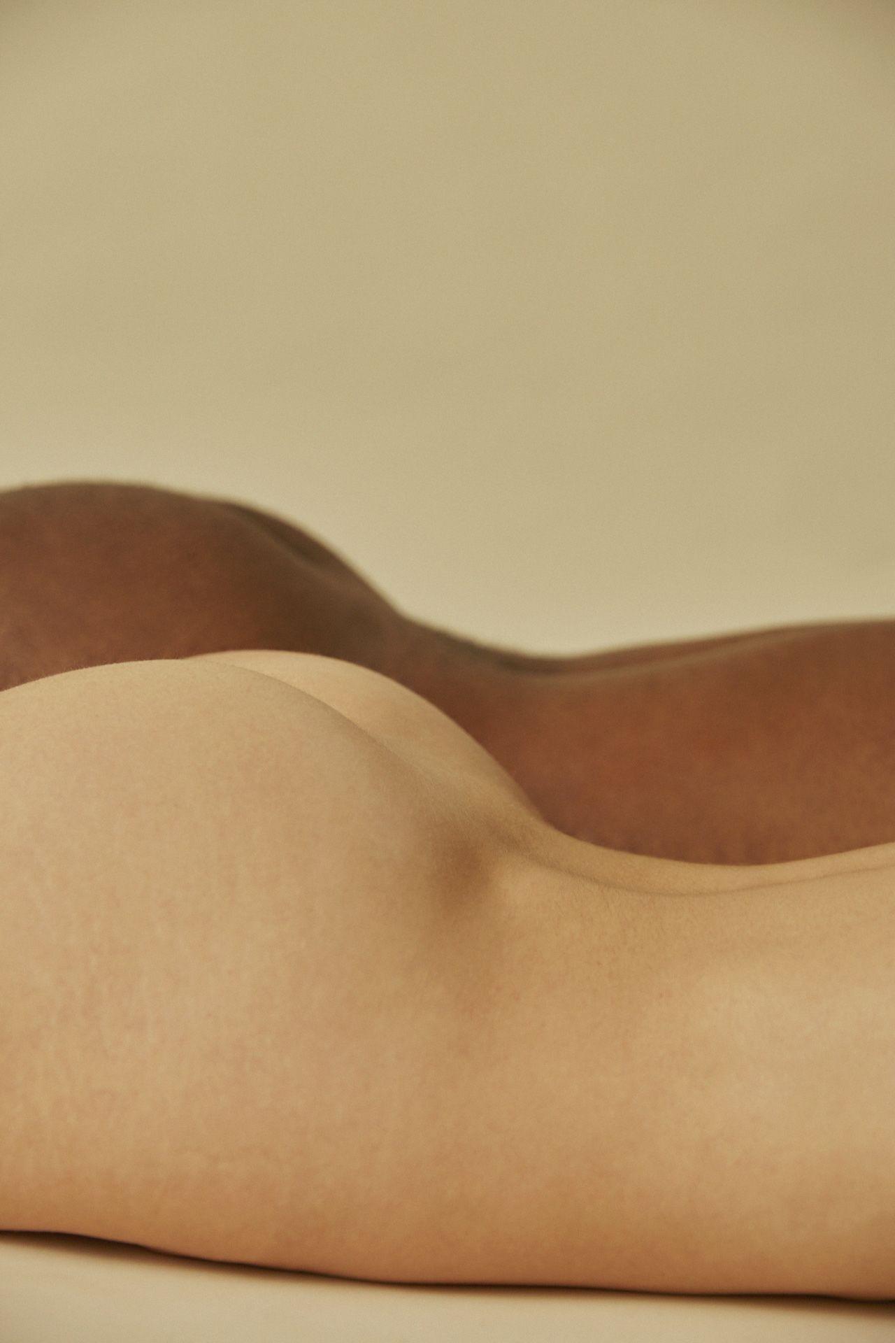 Deux corps côte à côte allongés sur le ventre, on ne voit que le bas du dos et les fesses.