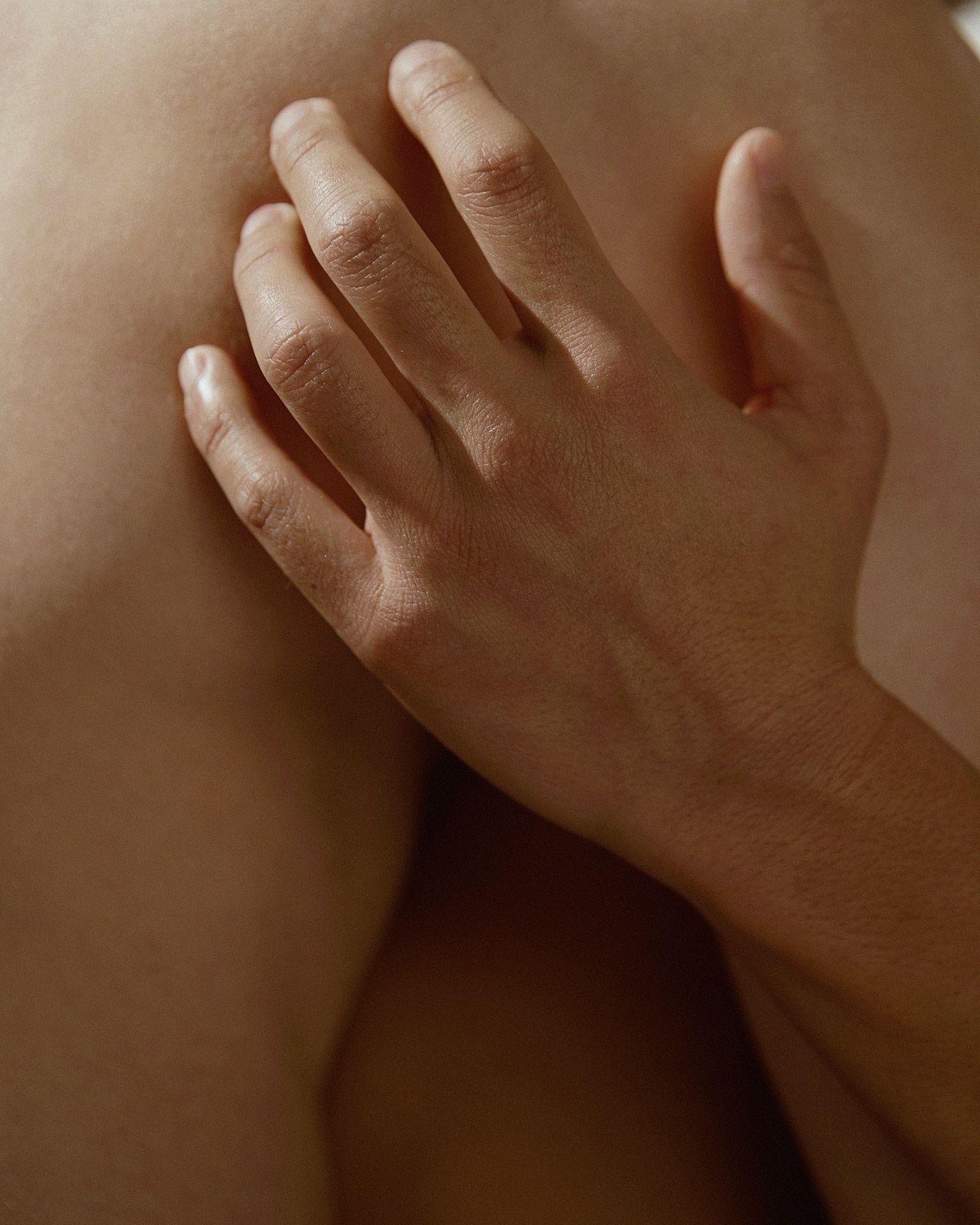 Close up shot of hand touching a naked torso.