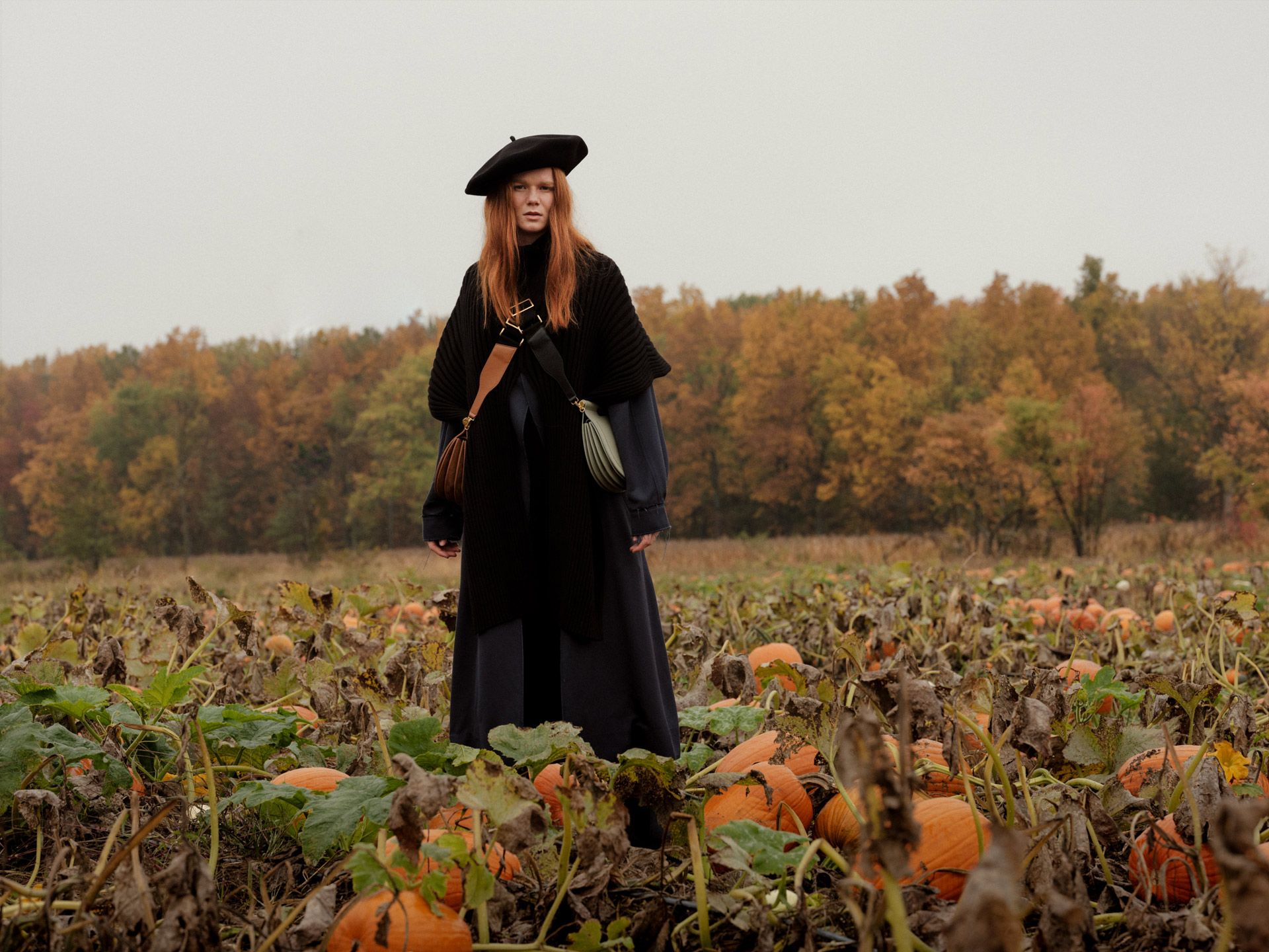 redhead female model standing all dressed in black in pumpkin patch with two crossbody leather purses photographed by Alexi Hobbs for Want Les Essentiels pre-Autumn Winter 2019 collection