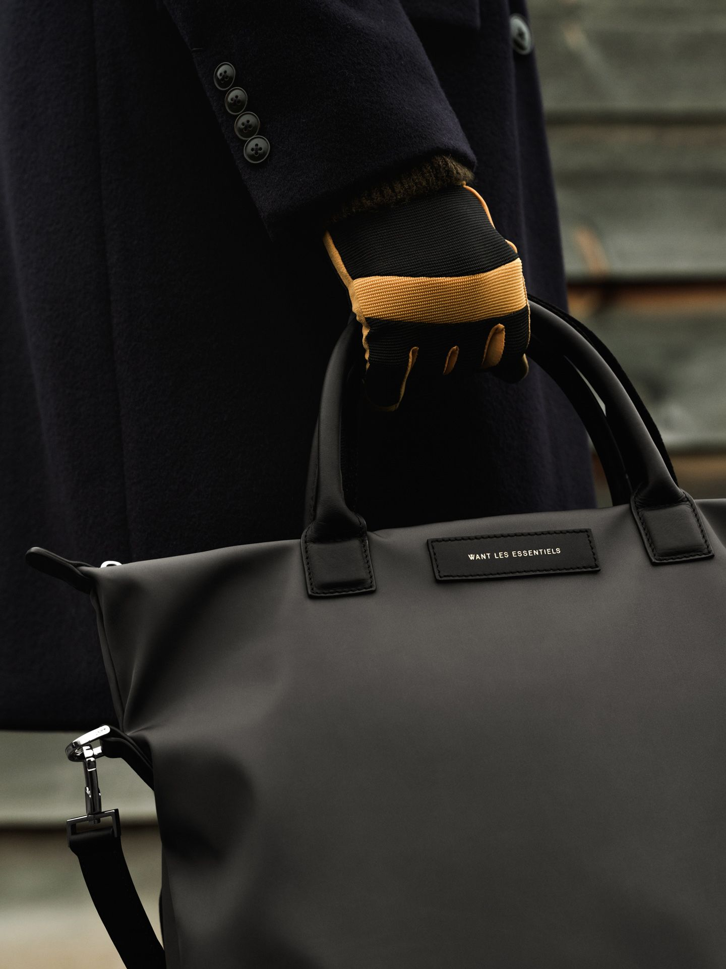 hand wearing yellow detailed glove holding bag photographed by Alexi Hobbs for Want Les Essentiels pre-Autumn Winter 2019 collection
