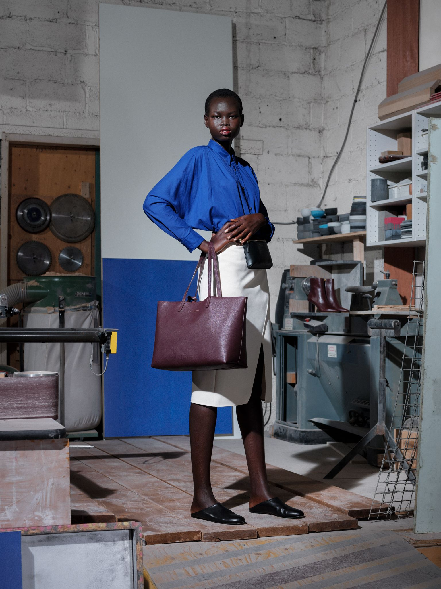 black female model wearing royal blue shirt white skirt and black leather shoes holding dark red purse and black fanny pack photographed by Alexi Hobbs for Want Les Essentiels Pre-Spring Summer 2019 collection